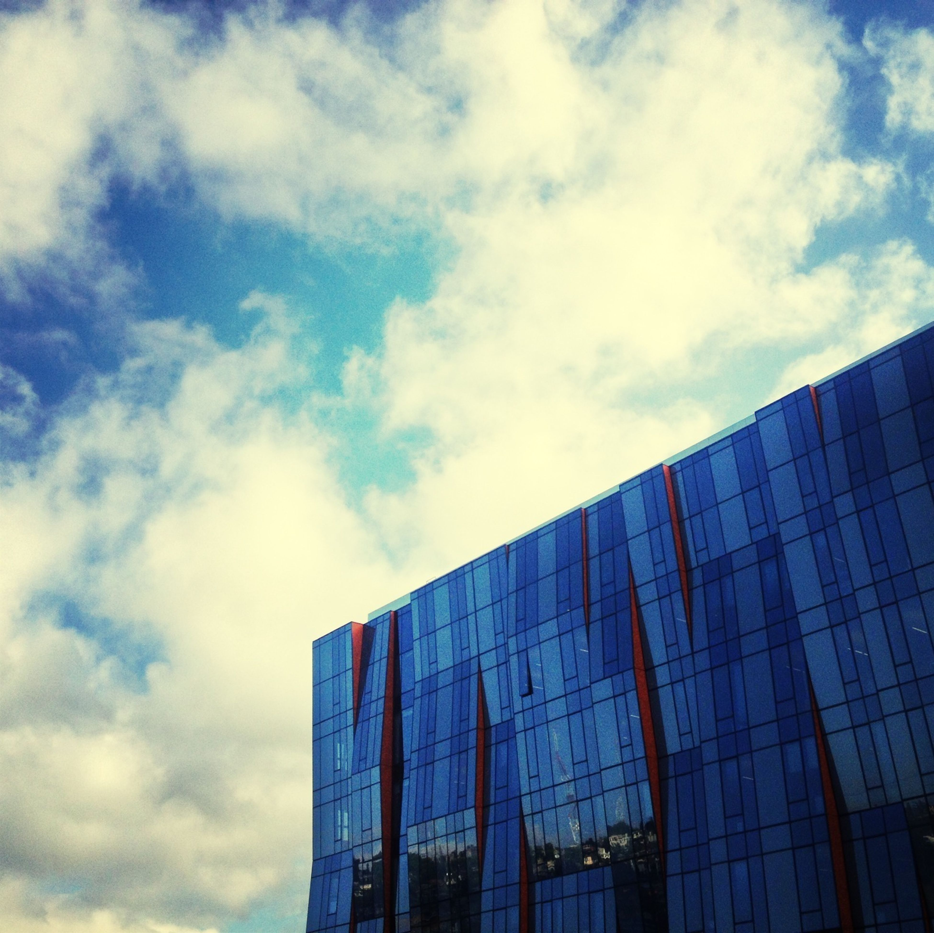 building exterior, architecture, built structure, low angle view, modern, office building, sky, city, glass - material, reflection, skyscraper, cloud - sky, building, tall - high, blue, cloud, window, day, tower, outdoors
