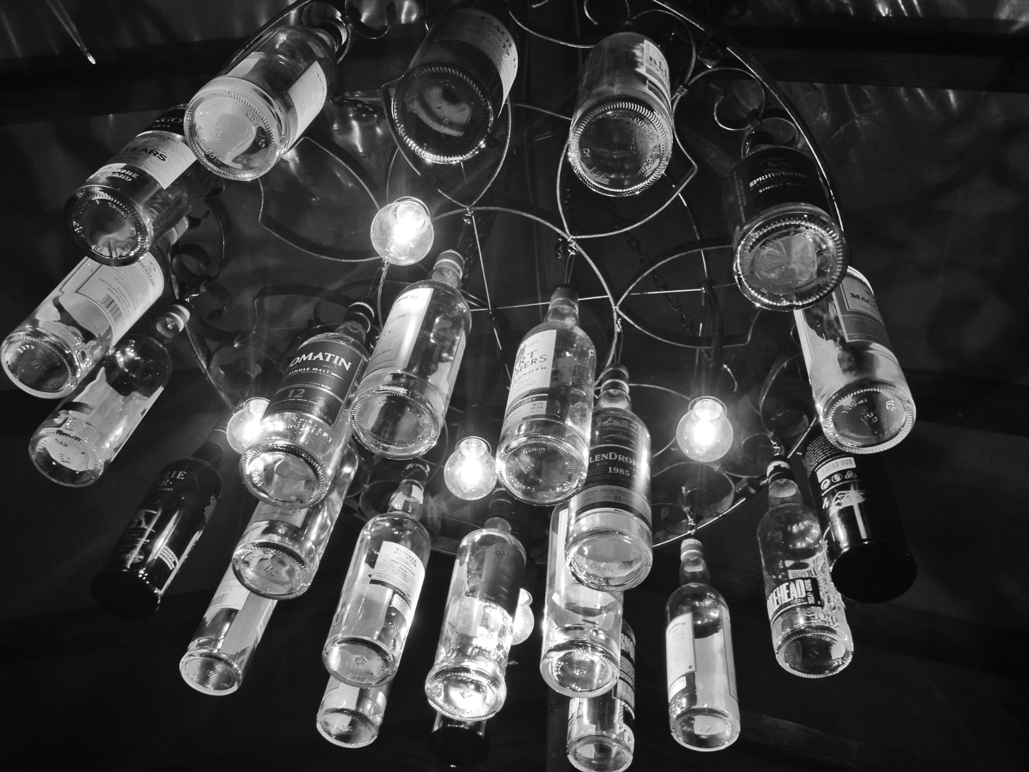 indoors, large group of objects, still life, variation, abundance, arrangement, close-up, illuminated, hanging, in a row, table, choice, electricity, technology, high angle view, lighting equipment, bottle, order, metal, no people