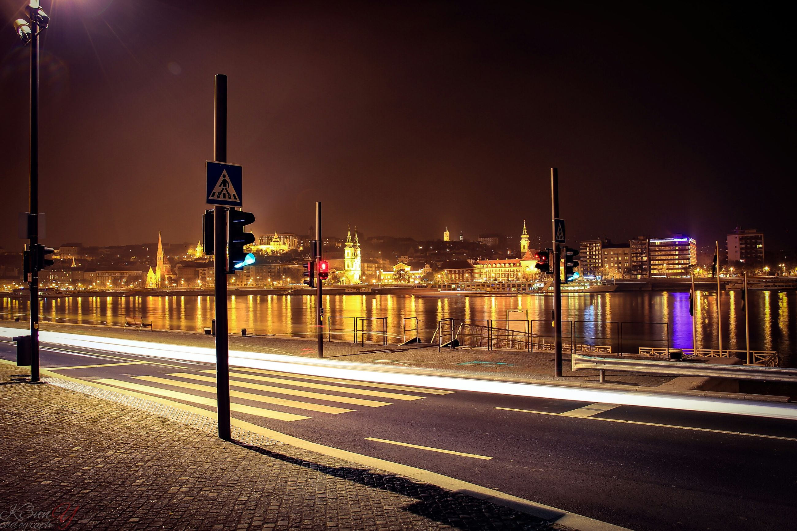 illuminated, building exterior, city, architecture, built structure, night, street light, street, road, the way forward, lighting equipment, transportation, sky, railing, city life, cityscape, empty, road marking, outdoors, clear sky