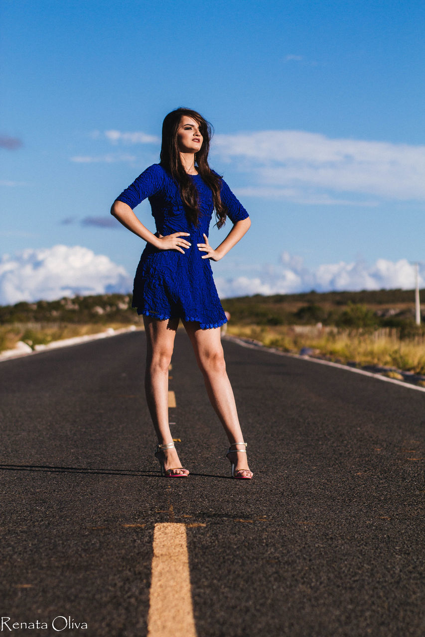 young adult, full length, road, young women, high heels, beautiful woman, real people, one person, sky, lifestyles, long hair, happiness, outdoors, blue, smiling, day, beauty in nature, nature, adult, people