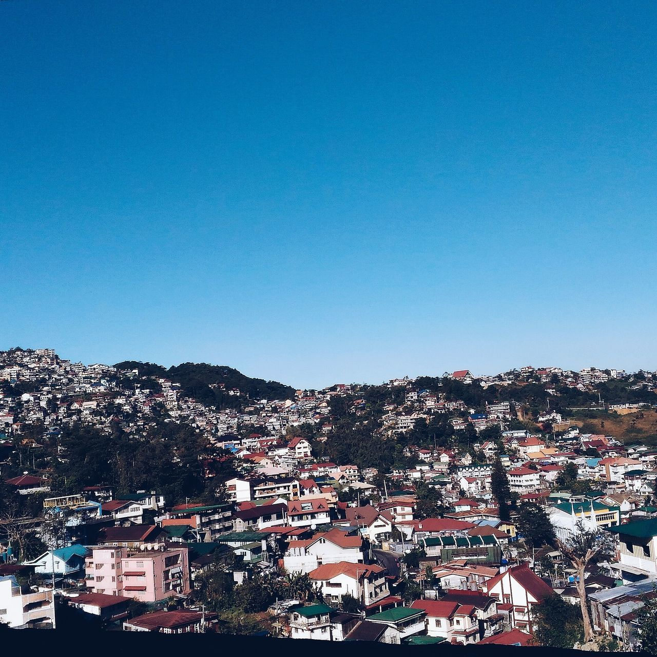 architecture, building exterior, built structure, clear sky, house, copy space, residential building, blue, day, no people, outdoors, high angle view, town, sunlight, tree, mountain, nature, cityscape, city, sky
