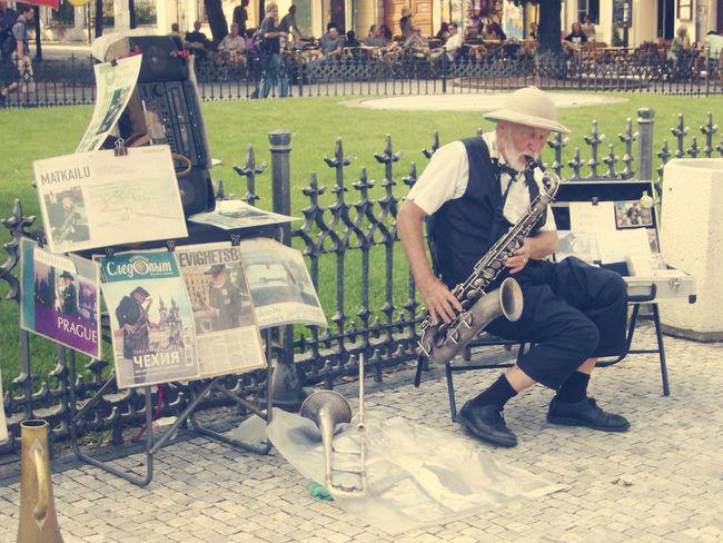 Street artist on Prague Artist Bench Day Grass Green Color Men Music Outdoors Prague Saxofone Sitting Square Street Artist Streetphotography