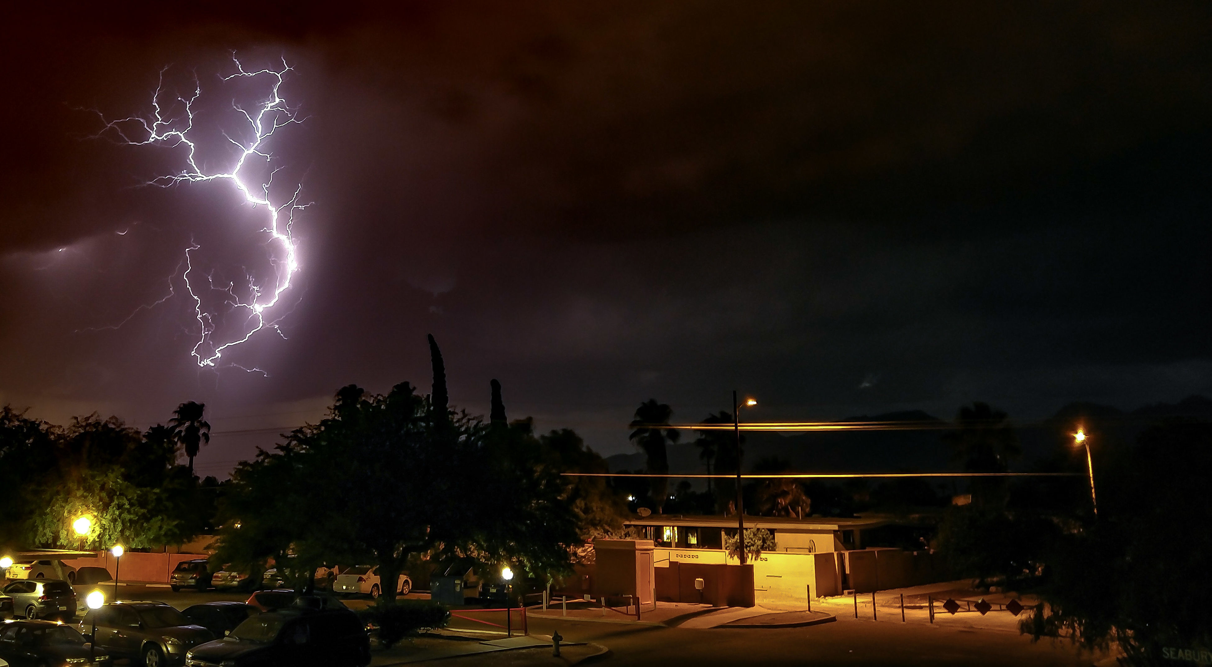 illuminated, night, tree, road, building exterior, celebration, architecture, built structure, firework - man made object, firework display, sky, exploding, outdoors, dark, lightning, sparks, place of worship, lit, tail light