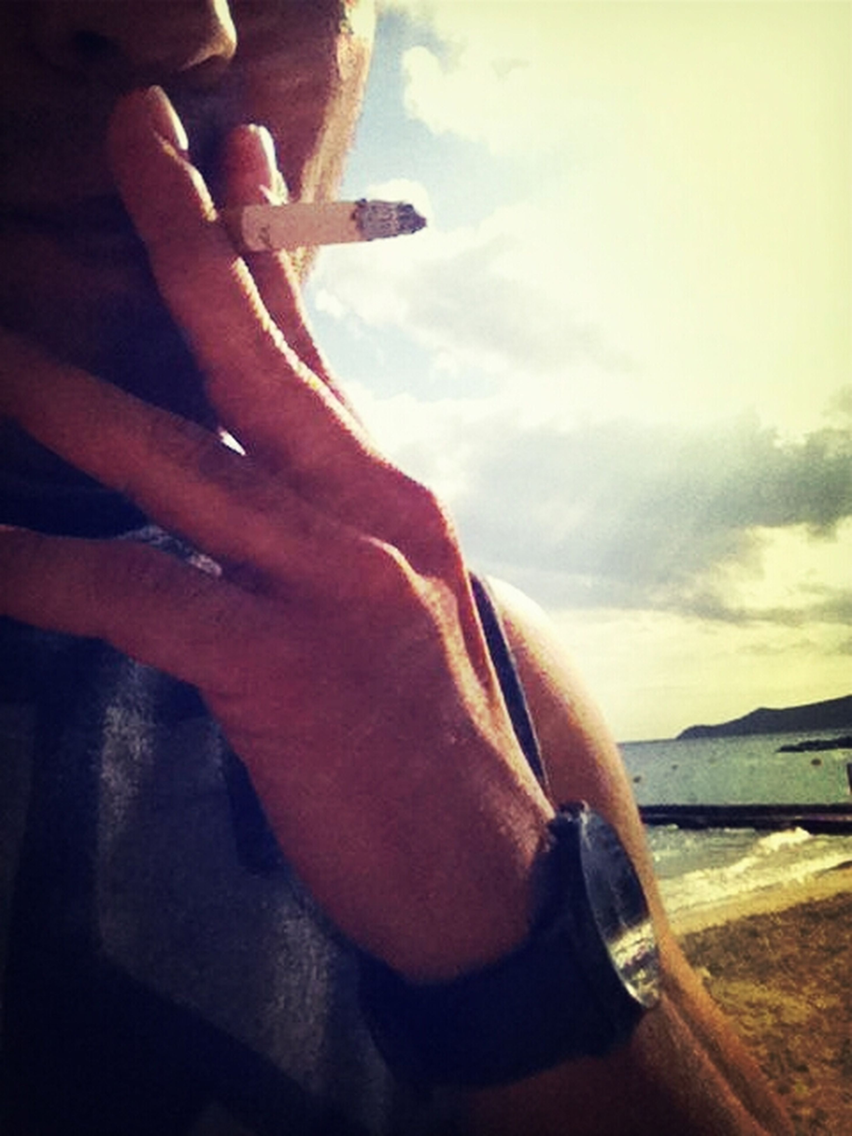 person, sky, lifestyles, part of, leisure activity, sea, cloud - sky, cropped, water, cloud, human finger, men, holding, sunlight, outdoors