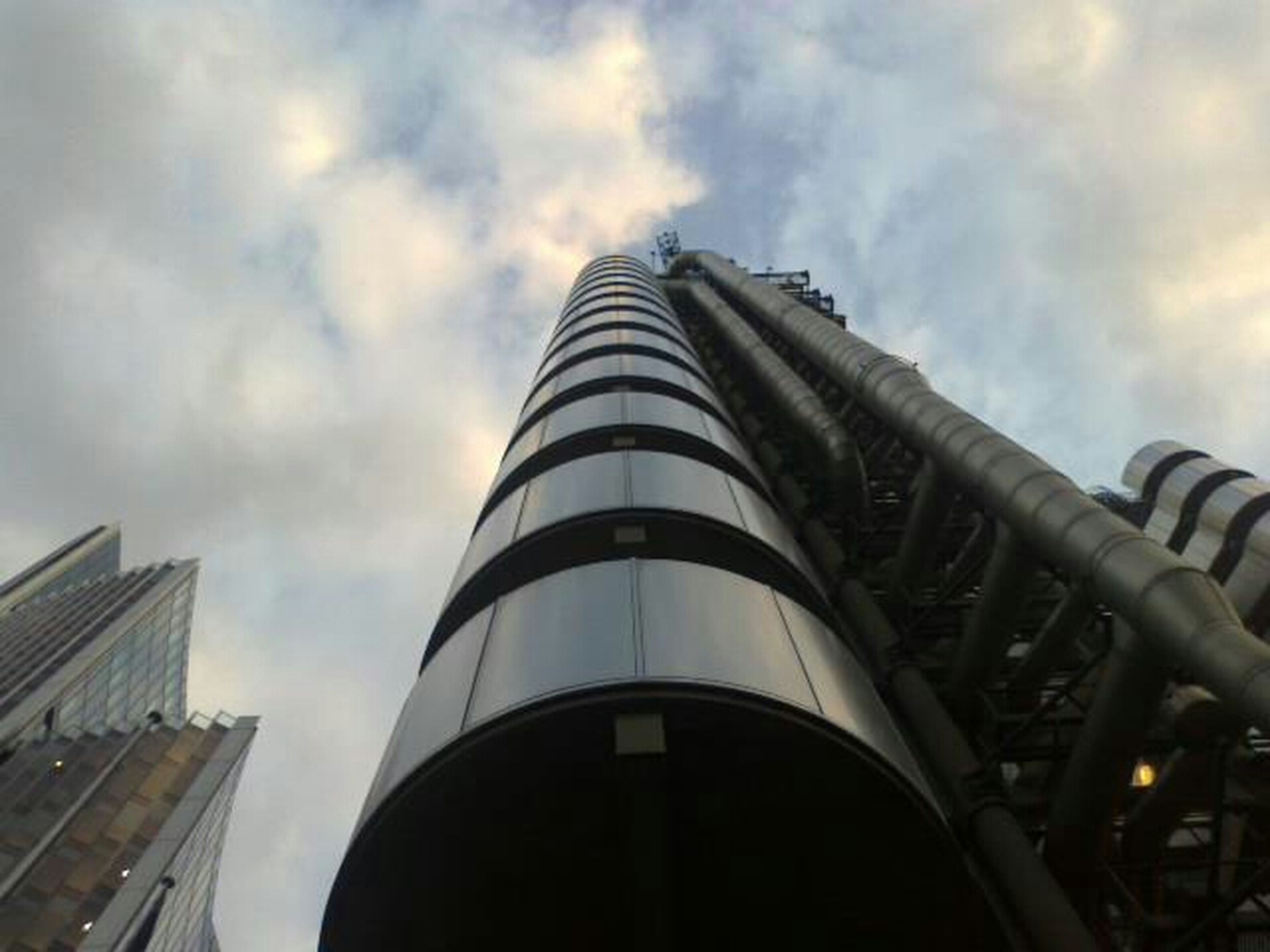 architecture, built structure, building exterior, low angle view, sky, modern, city, cloud - sky, tall - high, office building, skyscraper, tower, building, cloudy, cloud, day, outdoors, tall, capital cities, no people