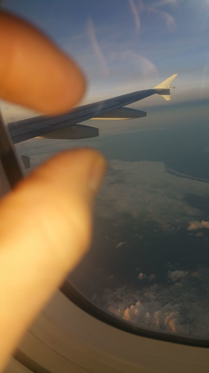 human hand, human body part, human finger, close-up, one person, airplane, selective focus, holding, indoors, real people, air vehicle, sky, sunset, flying, day, airplane wing, nature, people