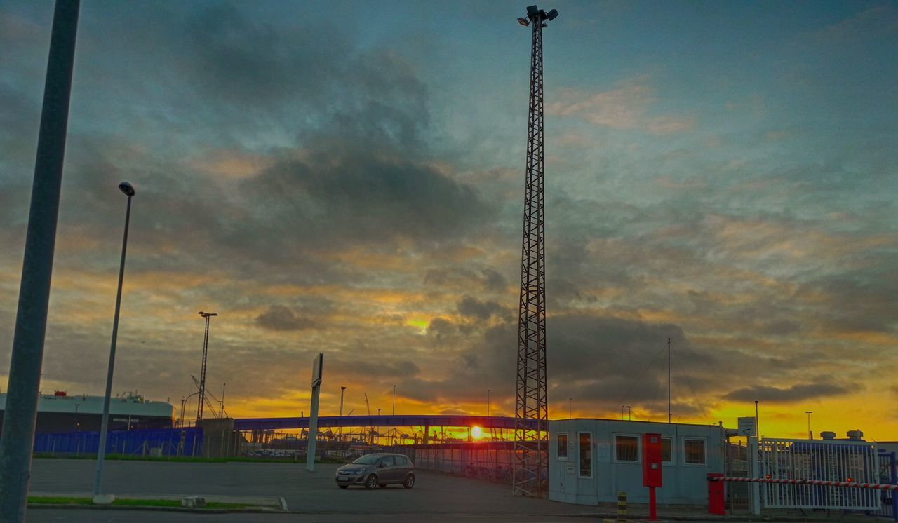sky, transportation, mode of transport, cloud - sky, land vehicle, sunset, car, outdoors, no people, built structure, road, nature, architecture, building exterior, day