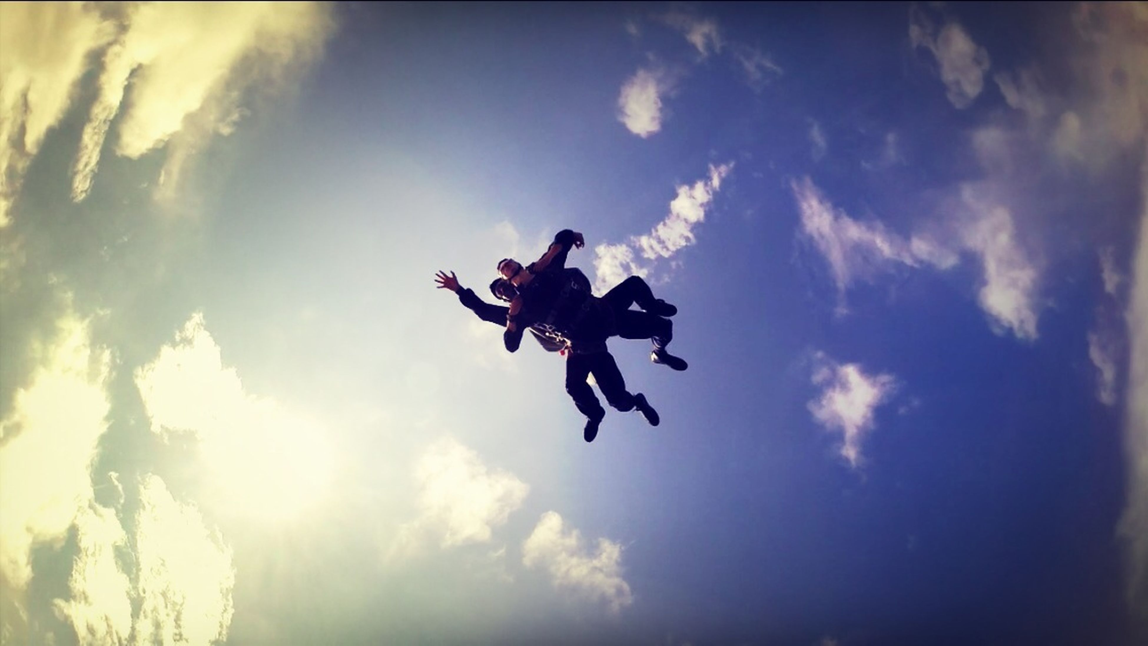 low angle view, sky, mid-air, cloud - sky, transportation, flying, air vehicle, mode of transport, airplane, cloud, silhouette, cloudy, on the move, blue, day, motion, extreme sports, freedom, travel, adventure