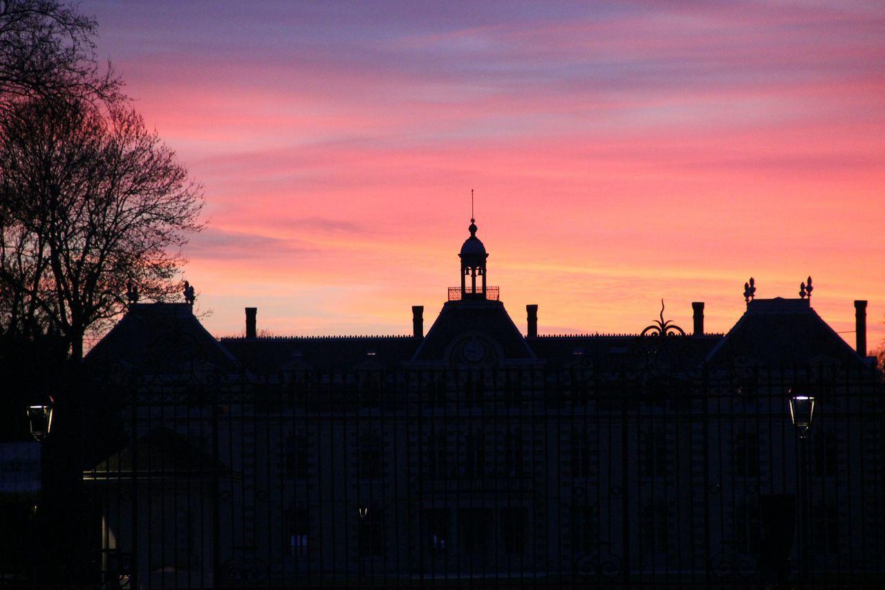 Silhouette castle against romantic sky at sunset