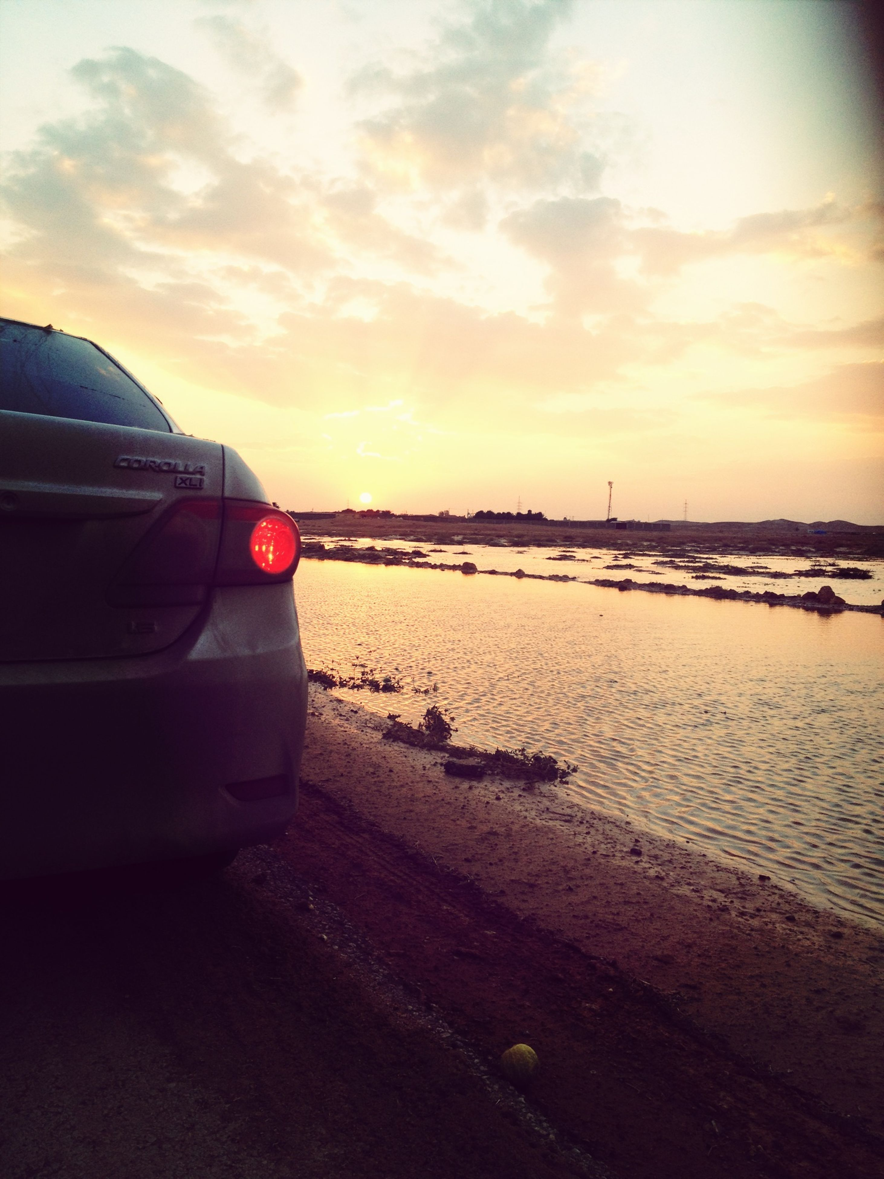 sunset, sky, transportation, sea, mode of transport, beach, orange color, water, cloud - sky, scenics, car, tranquility, tranquil scene, beauty in nature, land vehicle, nature, shore, horizon over water, cloud, sand