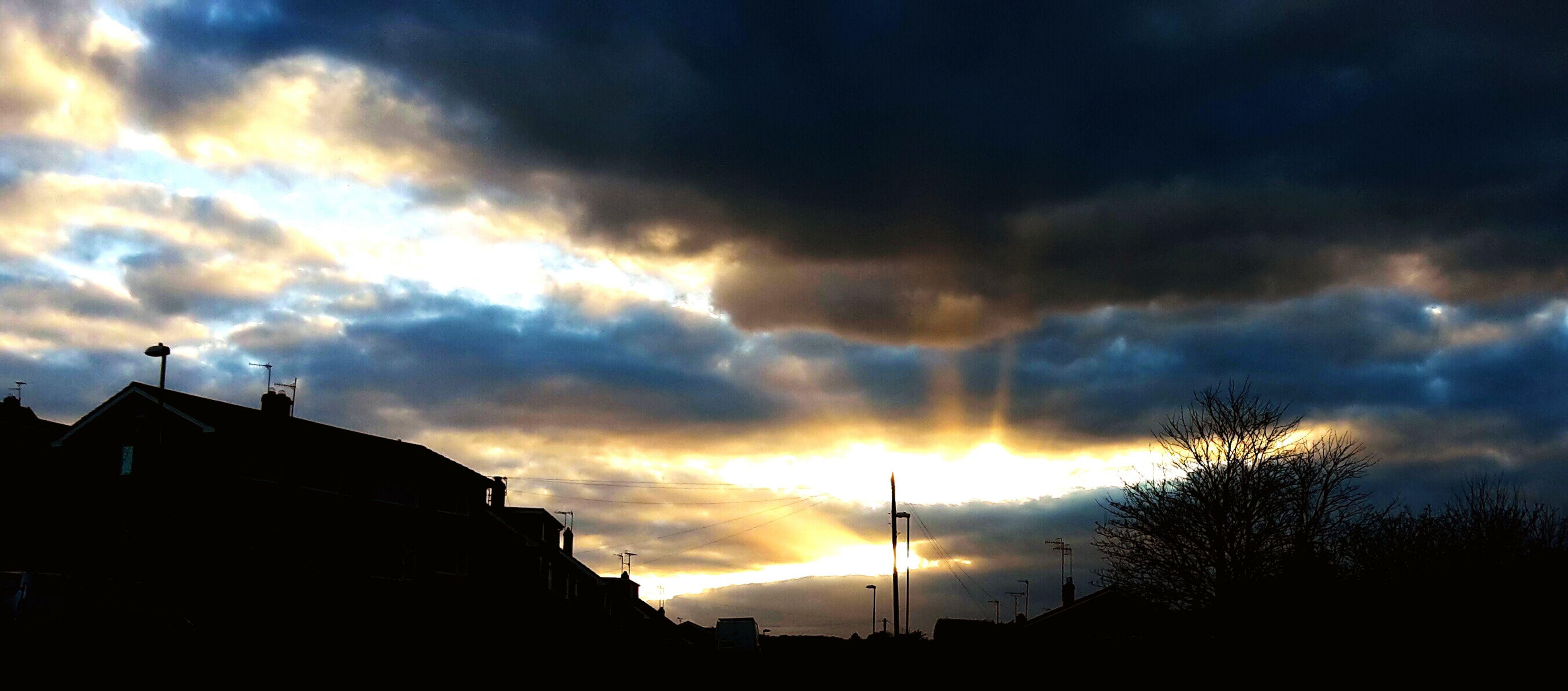 sunset, sky, building exterior, silhouette, architecture, cloud - sky, built structure, low angle view, cloudy, sun, cloud, house, dramatic sky, orange color, sunlight, beauty in nature, city, building, nature, sunbeam