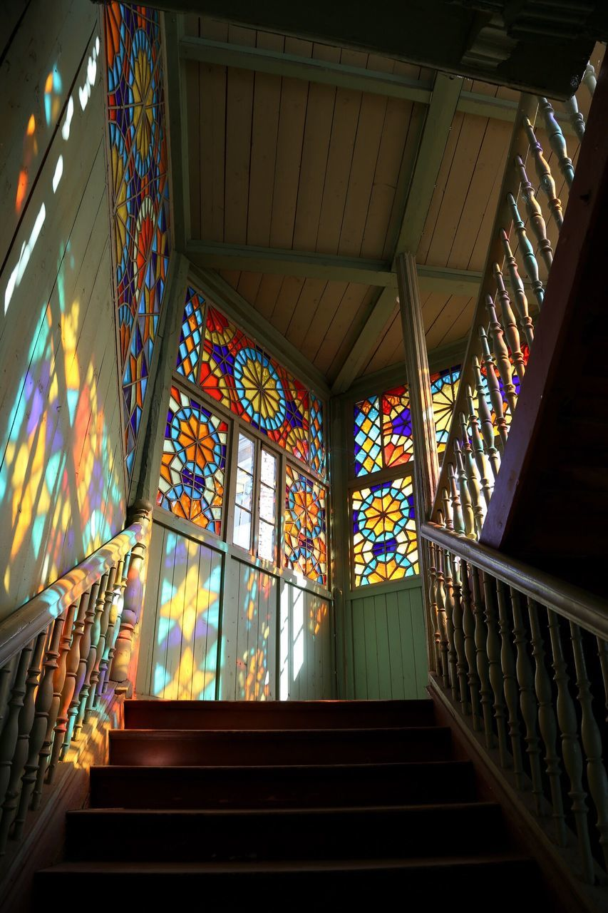 staircase, steps, railing, steps and staircases, architecture, indoors, built structure, multi colored, window, low angle view, no people, day