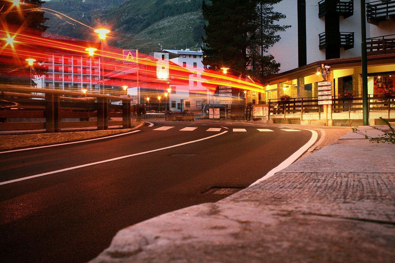 Light Trails On Illuminated Road By Sidewalk During Dusk