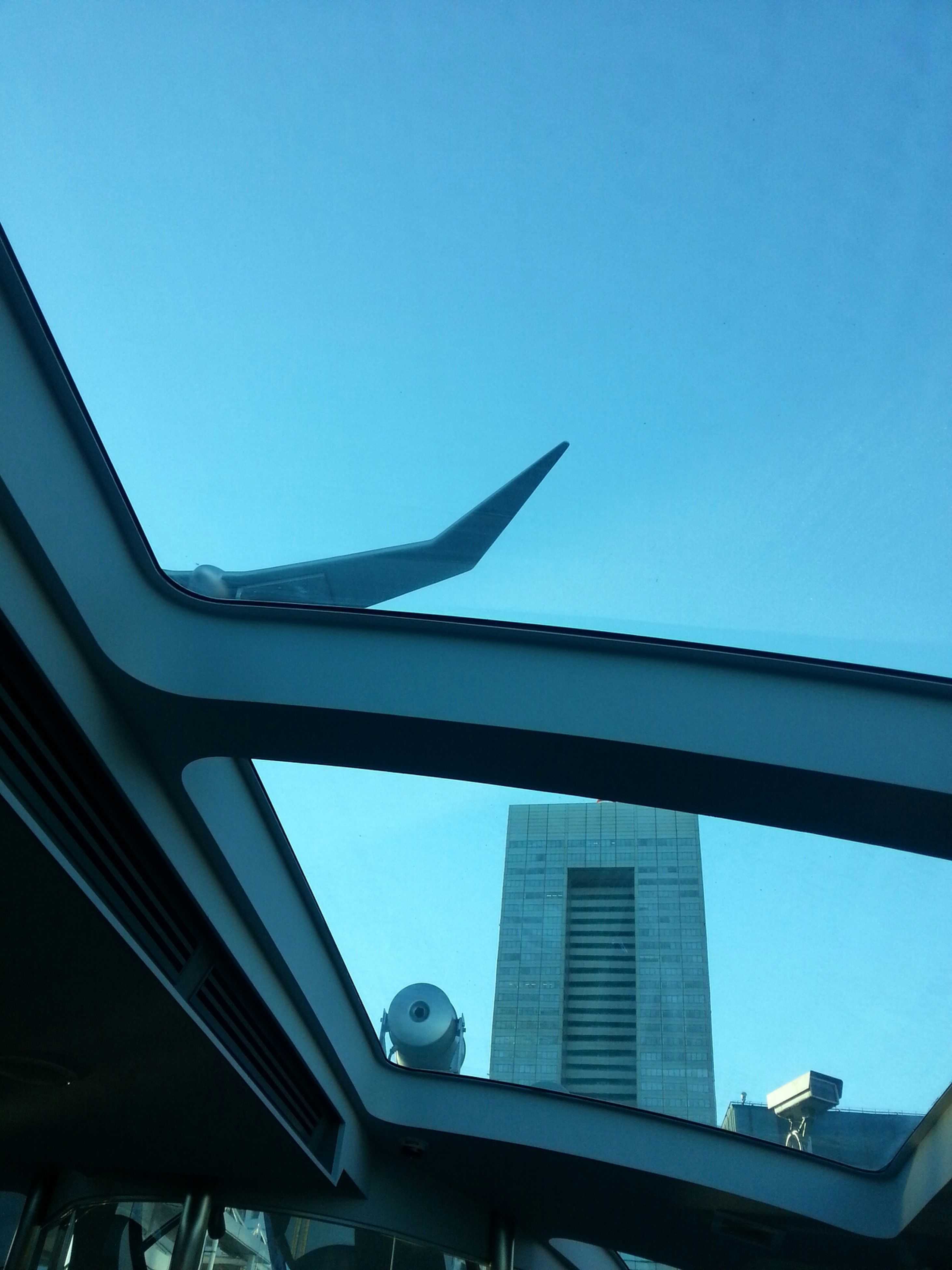 low angle view, architecture, built structure, clear sky, building exterior, blue, flying, bird, animal themes, animals in the wild, window, wildlife, sky, one animal, airplane, copy space, glass - material, building, day, mid-air