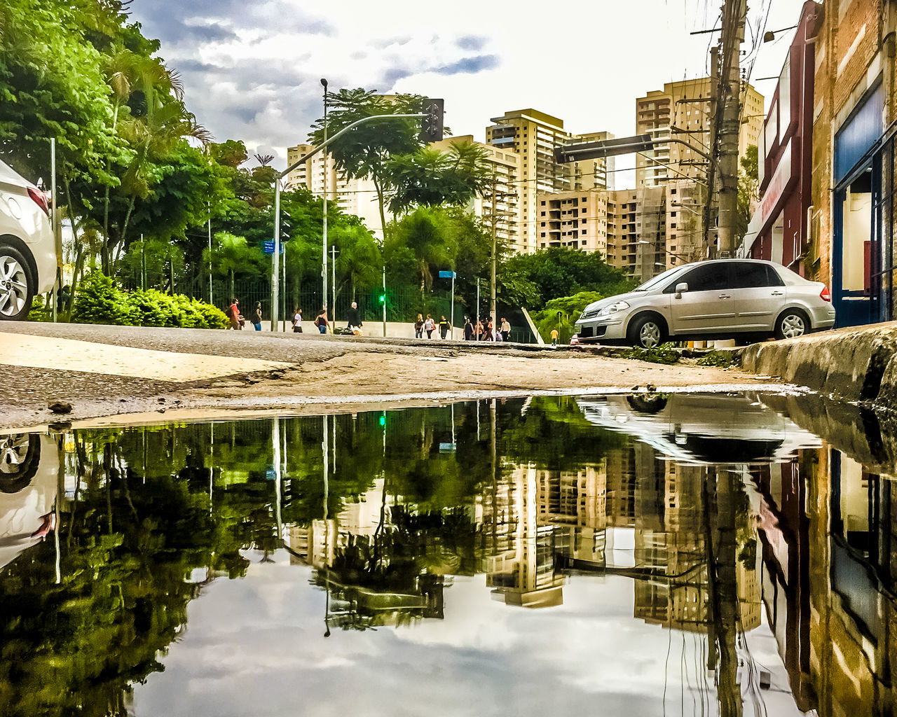 reflection, car, building exterior, transportation, mode of transport, land vehicle, architecture, water, built structure, day, tree, outdoors, sky, cloud - sky, puddle, city, no people