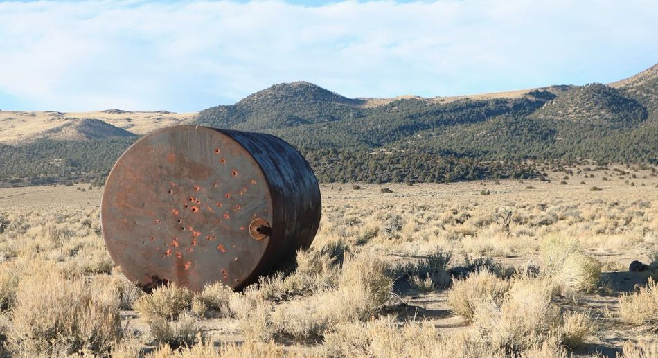 Empty and Forgotten Bullet Holes Rust Empty Tank Mountain Nature Landscape Field Day No People Outdoors Grass Scenics Beauty In Nature Arid Climate Sky
