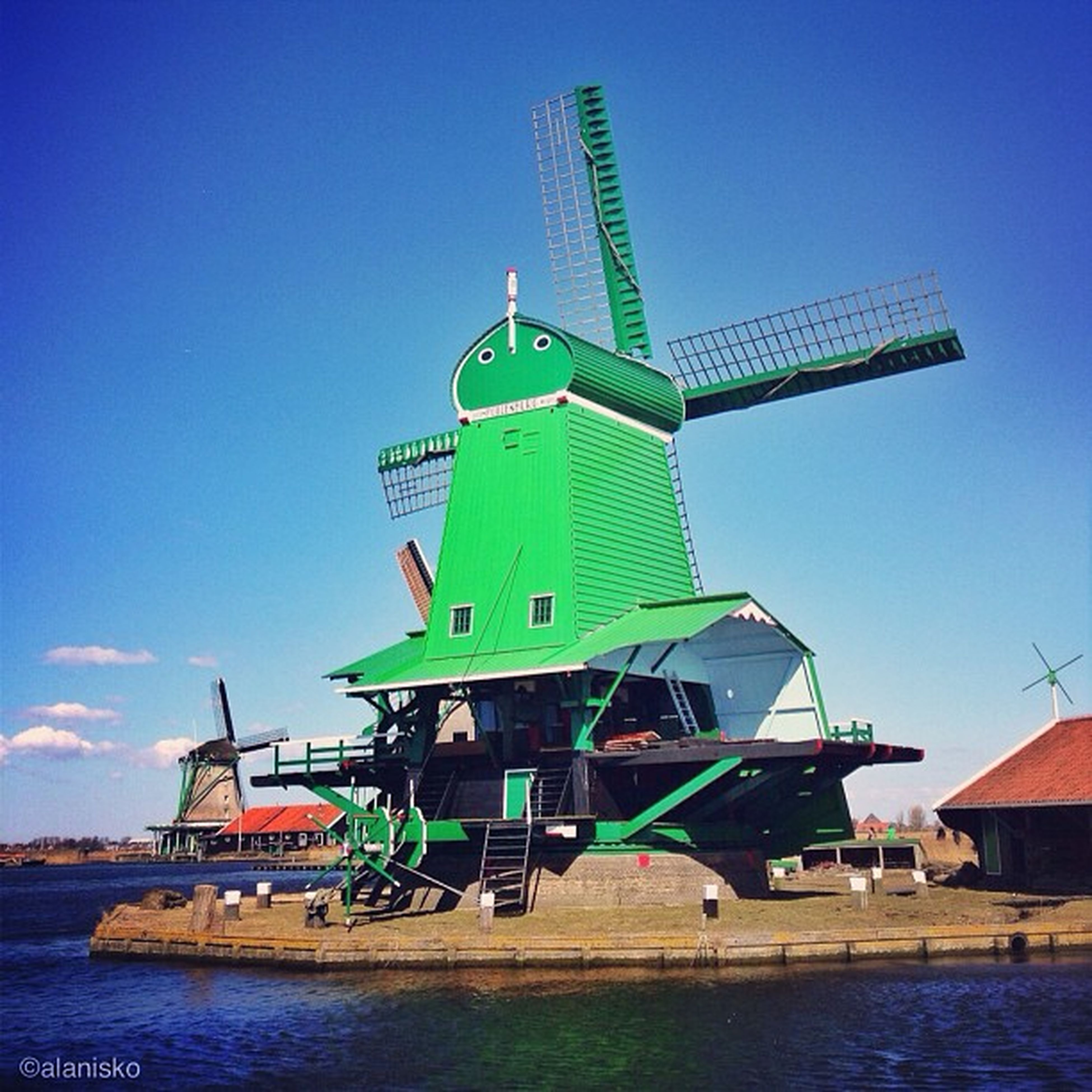 water, clear sky, blue, built structure, waterfront, architecture, copy space, building exterior, sea, transportation, lake, crane - construction machinery, industry, river, day, traditional windmill, nautical vessel, outdoors, harbor, renewable energy