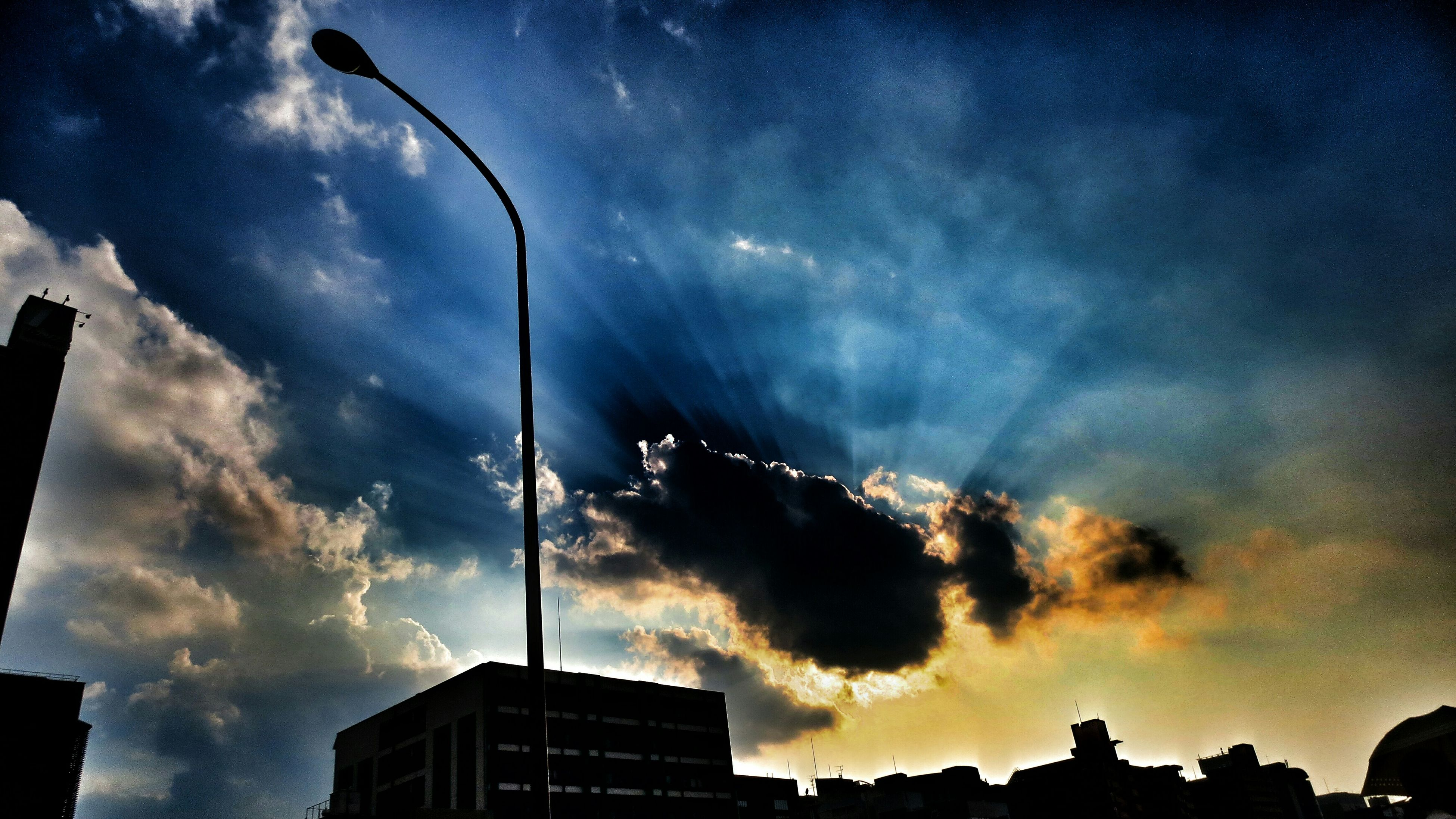 low angle view, sky, cloud - sky, built structure, building exterior, silhouette, street light, architecture, cloudy, cloud, lighting equipment, high section, weather, dusk, building, outdoors, sunset, no people, overcast, nature