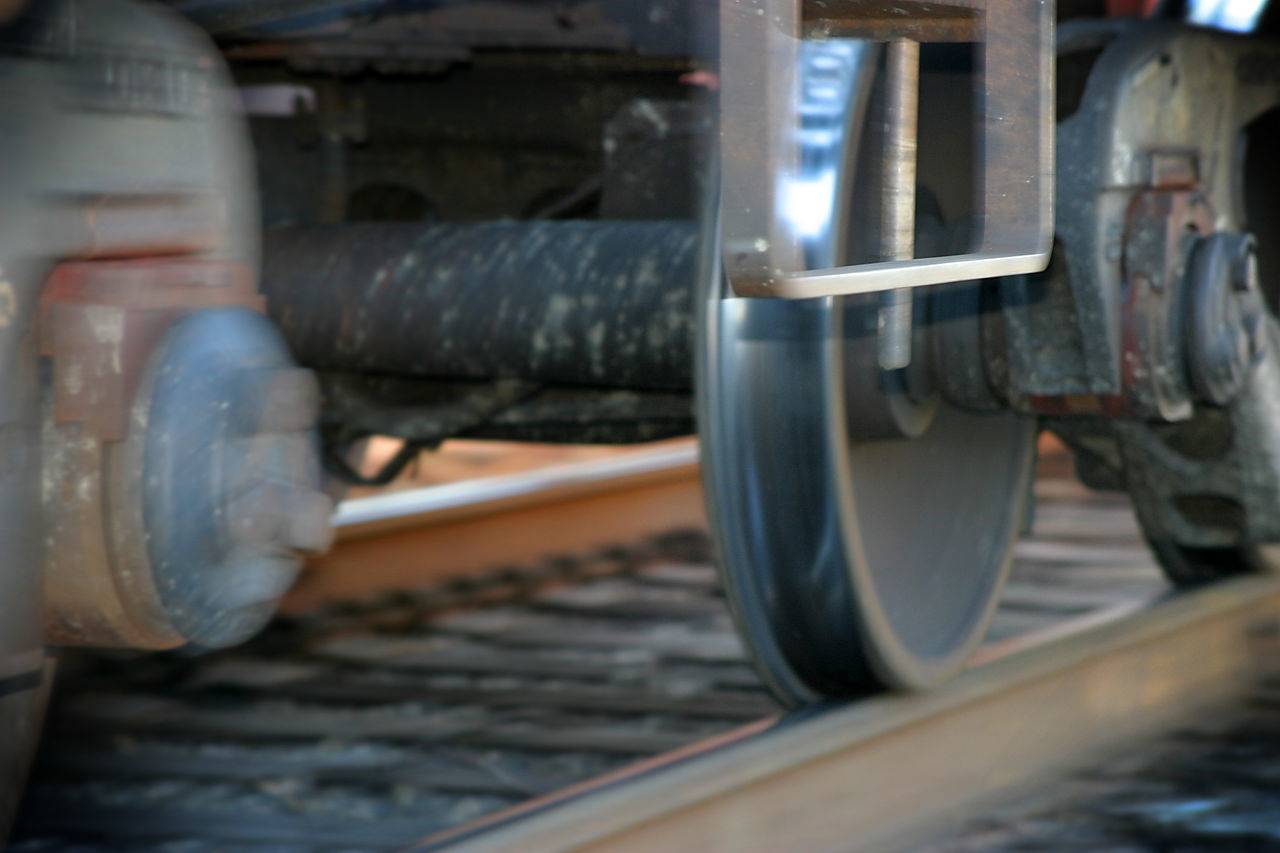 Train Tires Photo of a moving train with part of the photo blurred to show the movement Cargo Carriage Freight Industrial Industry Iron Metal Motion Moving Rail Railroad Rails Railway Rust Shipment Speed Tire Track Tracks Train Transit Transport Transportation Wagon