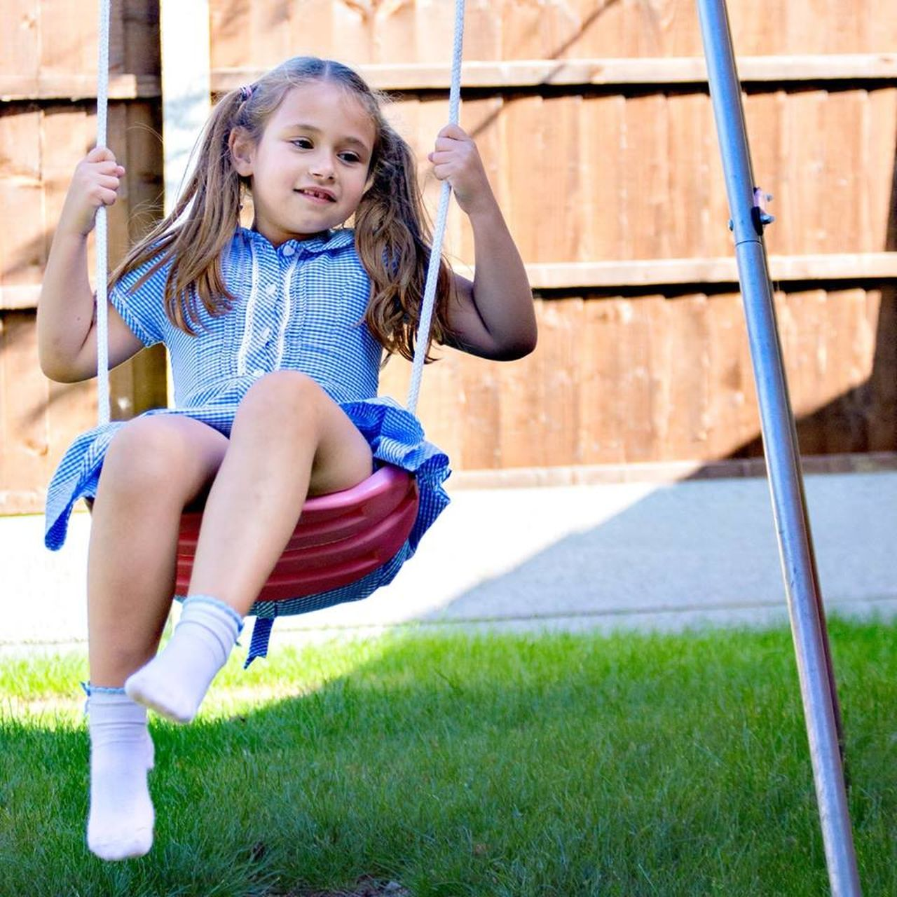 childhood, girls, child, full length, grass, playground, one person, children only, cute, sitting, happiness, outdoors, casual clothing, looking at camera, one girl only, day, portrait, smiling, elementary age, swing, lifestyles, real people, blond hair, people