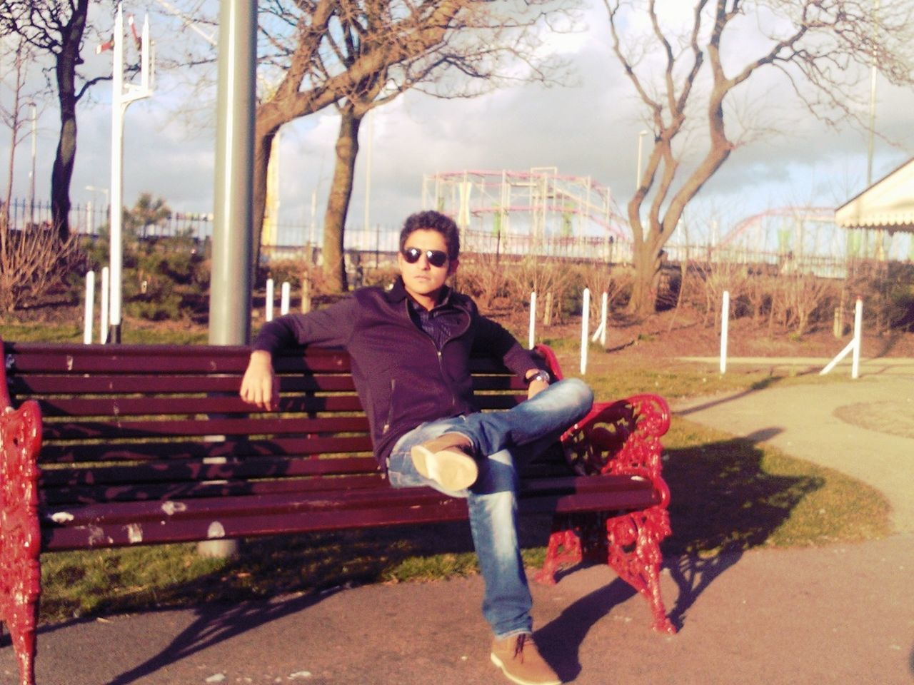 full length, looking at camera, one person, young adult, sunglasses, sitting, portrait, tree, one young man only, casual clothing, one man only, day, young men, only men, outdoors, leisure activity, smiling, shadow, relaxation, real people, adults only, bare tree, adult, sky, people