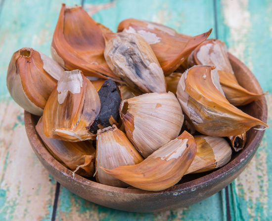 Caramelized cloves of black garlic over wooden background Black Bulb Caramalized Cloves Delicious Fermentation Flavour Food Garlic Ingredients Preserve Seasoning Spices Sweet