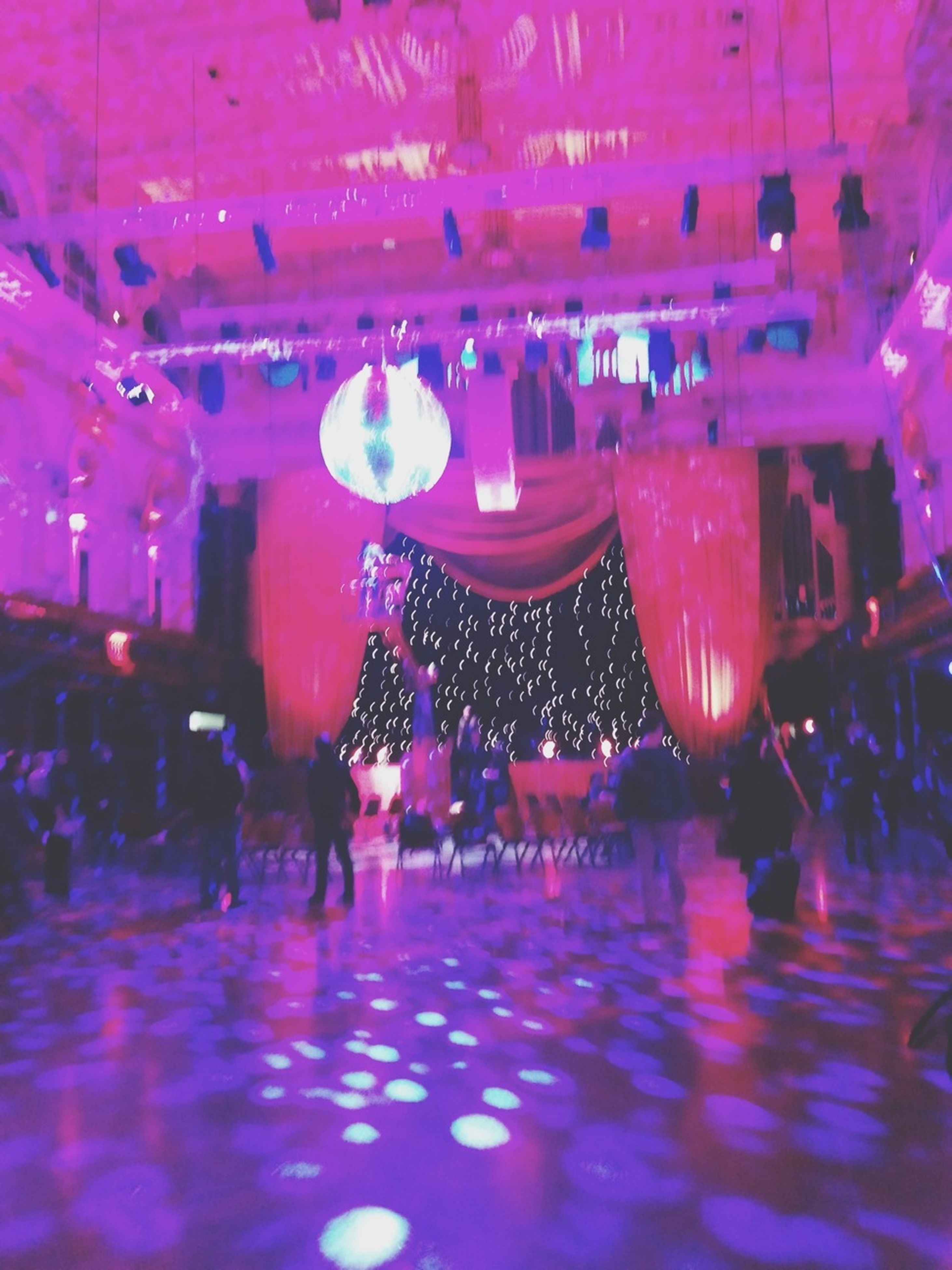 large group of people, illuminated, indoors, person, arts culture and entertainment, celebration, men, lifestyles, leisure activity, enjoyment, night, crowd, lighting equipment, decoration, built structure, fun, pink color, reflection, mixed age range