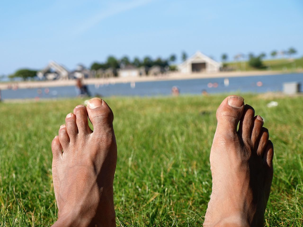 barefoot, human foot, focus on foreground, human body part, real people, human leg, low section, grass, personal perspective, leisure activity, day, relaxation, outdoors, sole of foot, one person, men, water, close-up, lifestyles, vacations, human hand, sky, people