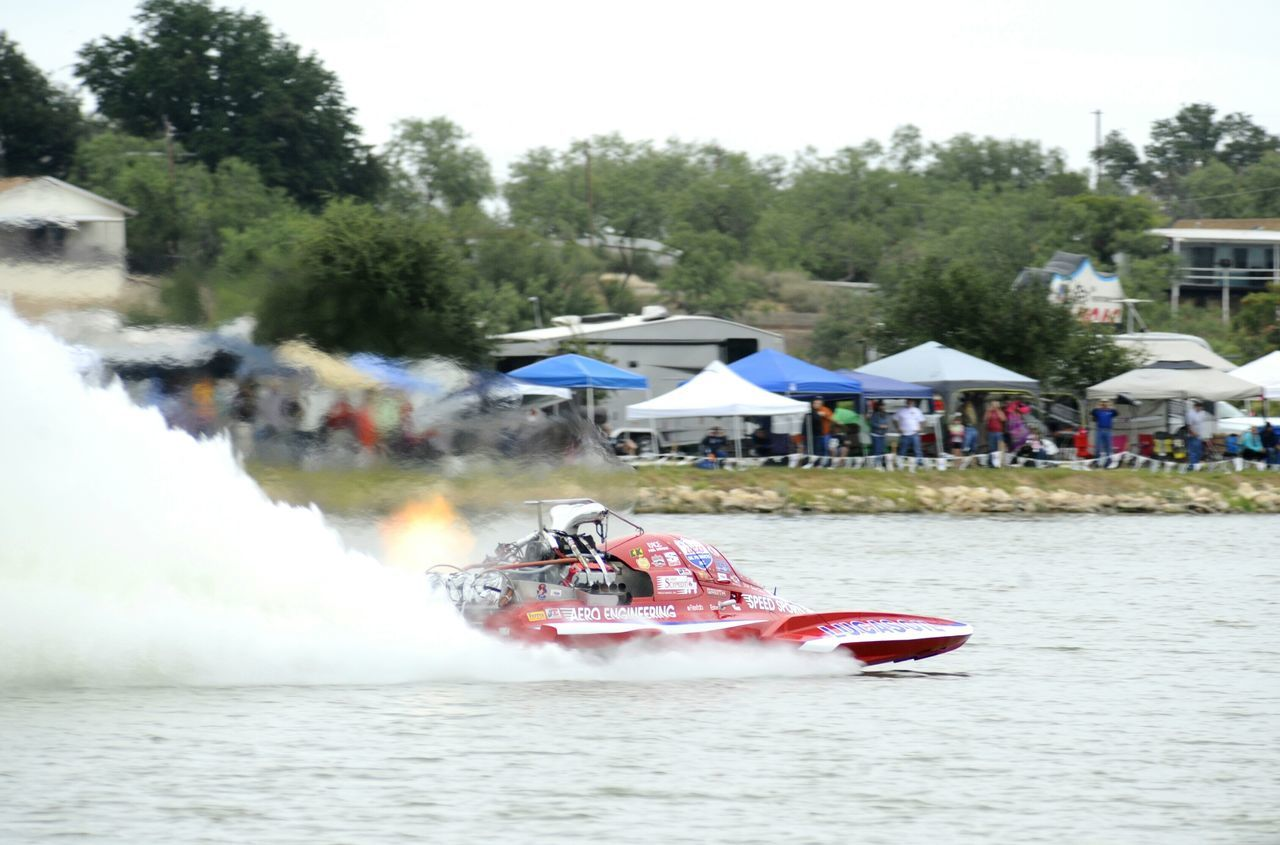 day, outdoors, real people, transportation, water, large group of people, nautical vessel, mode of transport, tree, speed, leisure activity, motion, event, group of people, men, nature, jet boat, sports race, sky, people