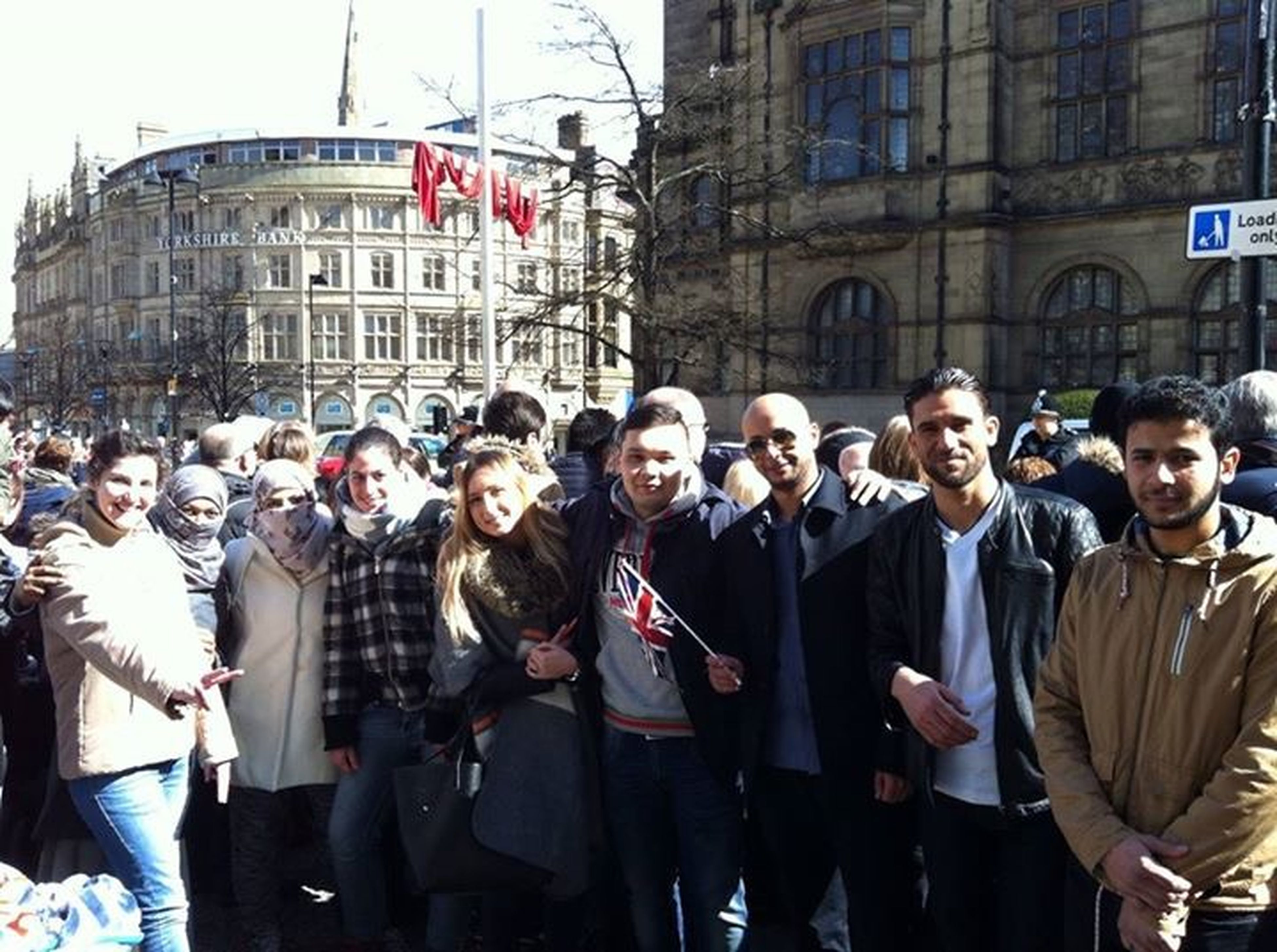 large group of people, lifestyles, building exterior, men, architecture, leisure activity, person, built structure, casual clothing, crowd, city, togetherness, city life, street, happiness, young adult, standing, day, mixed age range