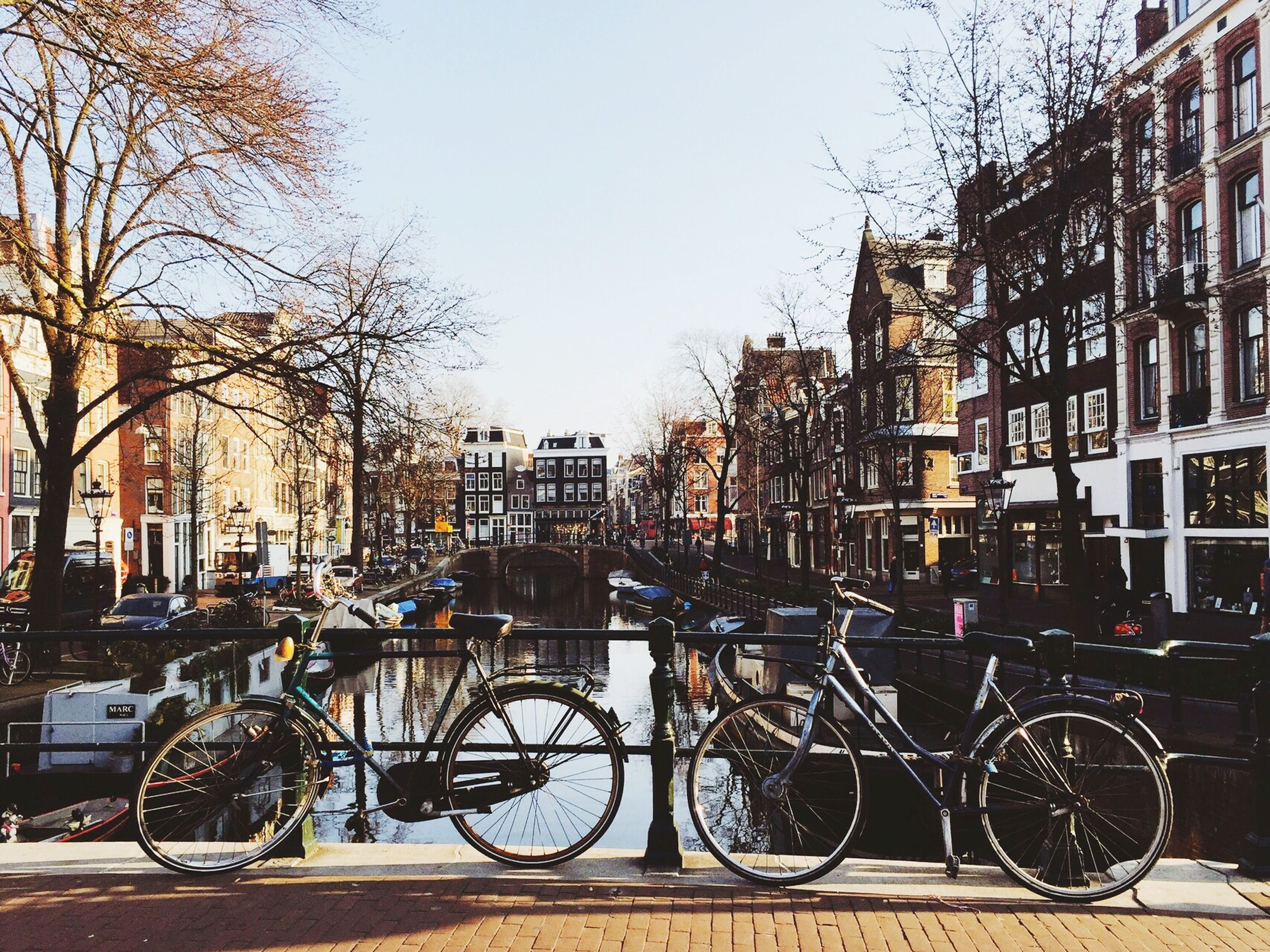 bicycle, building exterior, transportation, mode of transport, architecture, land vehicle, built structure, parked, parking, city, stationary, street, tree, car, clear sky, railing, canal, residential structure, city life, residential building