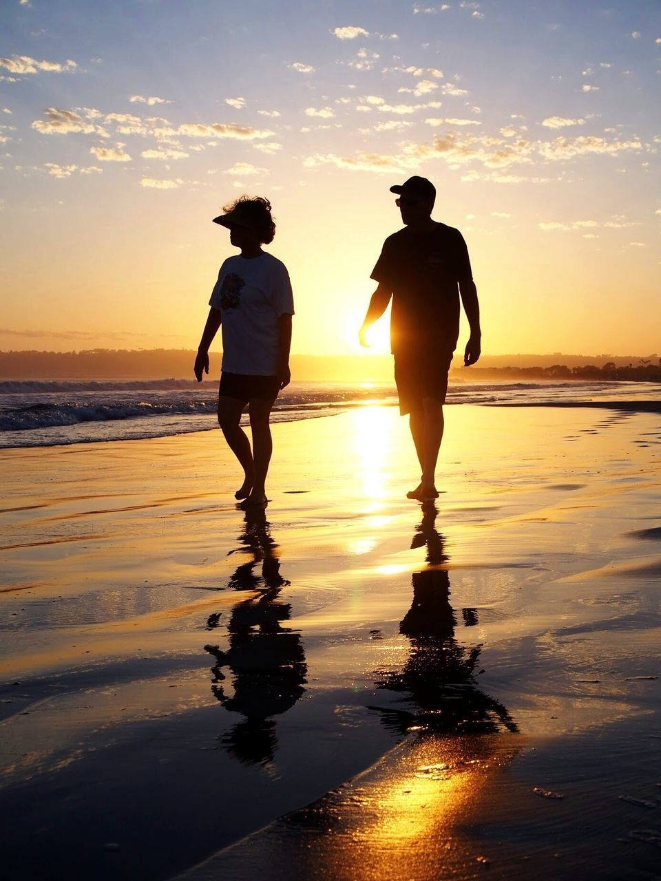 sunset, two people, sea, reflection, silhouette, water, beach, nature, sky, real people, beauty in nature, leisure activity, scenics, full length, men, standing, togetherness, horizon over water, sun, walking, vacations, love, tranquility, couple - relationship, lifestyles, sunlight, bonding, outdoors, women