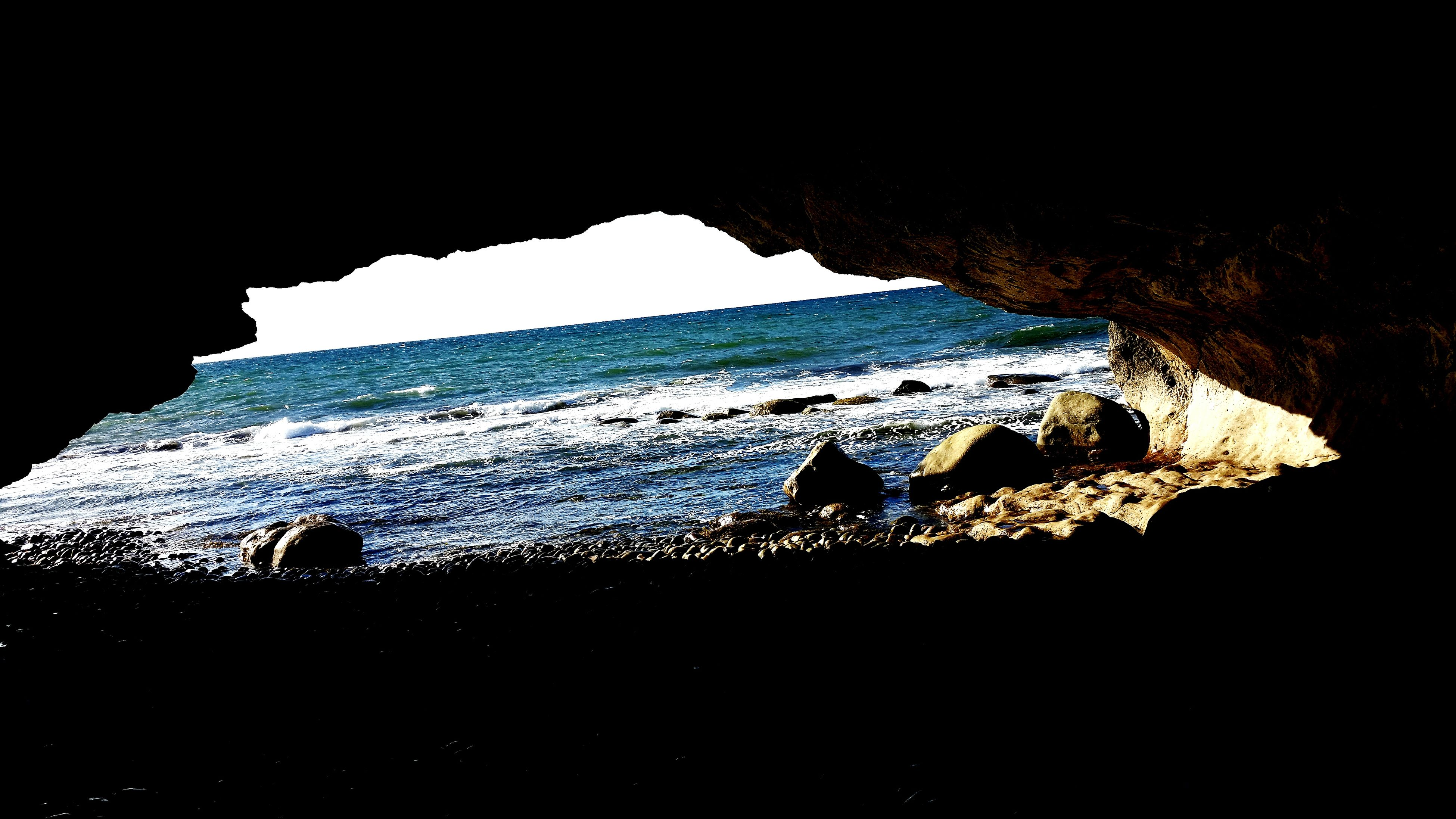 sea, water, horizon over water, scenics, beach, rock formation, beauty in nature, rock - object, tranquility, tranquil scene, sky, nature, shore, silhouette, idyllic, coastline, cliff, indoors, rock, cave