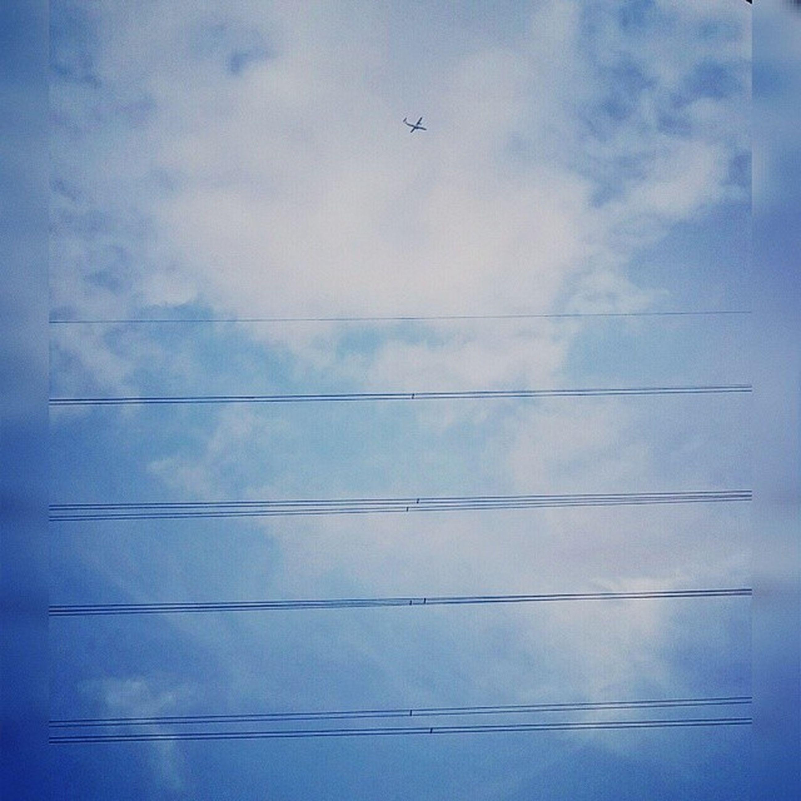 low angle view, sky, blue, cloud - sky, flying, cloud, bird, no people, nature, cloudy, day, outdoors, backgrounds, power line, airplane, beauty in nature, electricity, animal themes, tranquility, mid-air