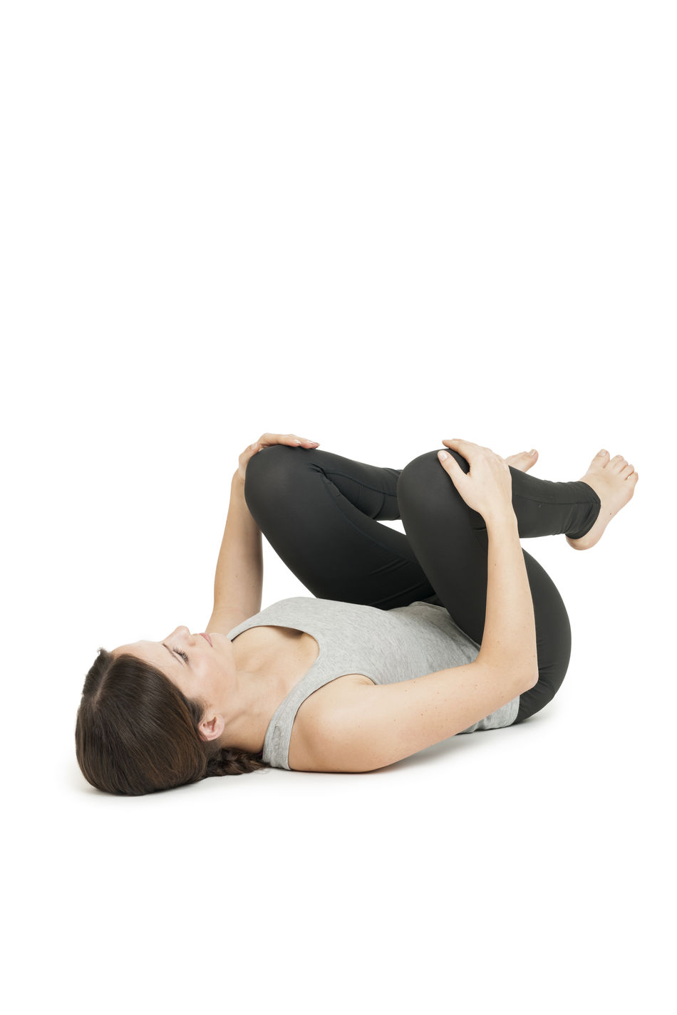 """Flat angular full body view of a lying on the back young woman in yoga position """"happy baby"""" (anada balasana) on a white background. Anada Balasana Añada Balasana Copy Space Exercising Flexibility Full Length Happy Baby Happy Child  Hold Knees Lying On Back One Person People Sporty Studio Shot White Background Women Yoga Yoga Position Young Adult Young Women"""