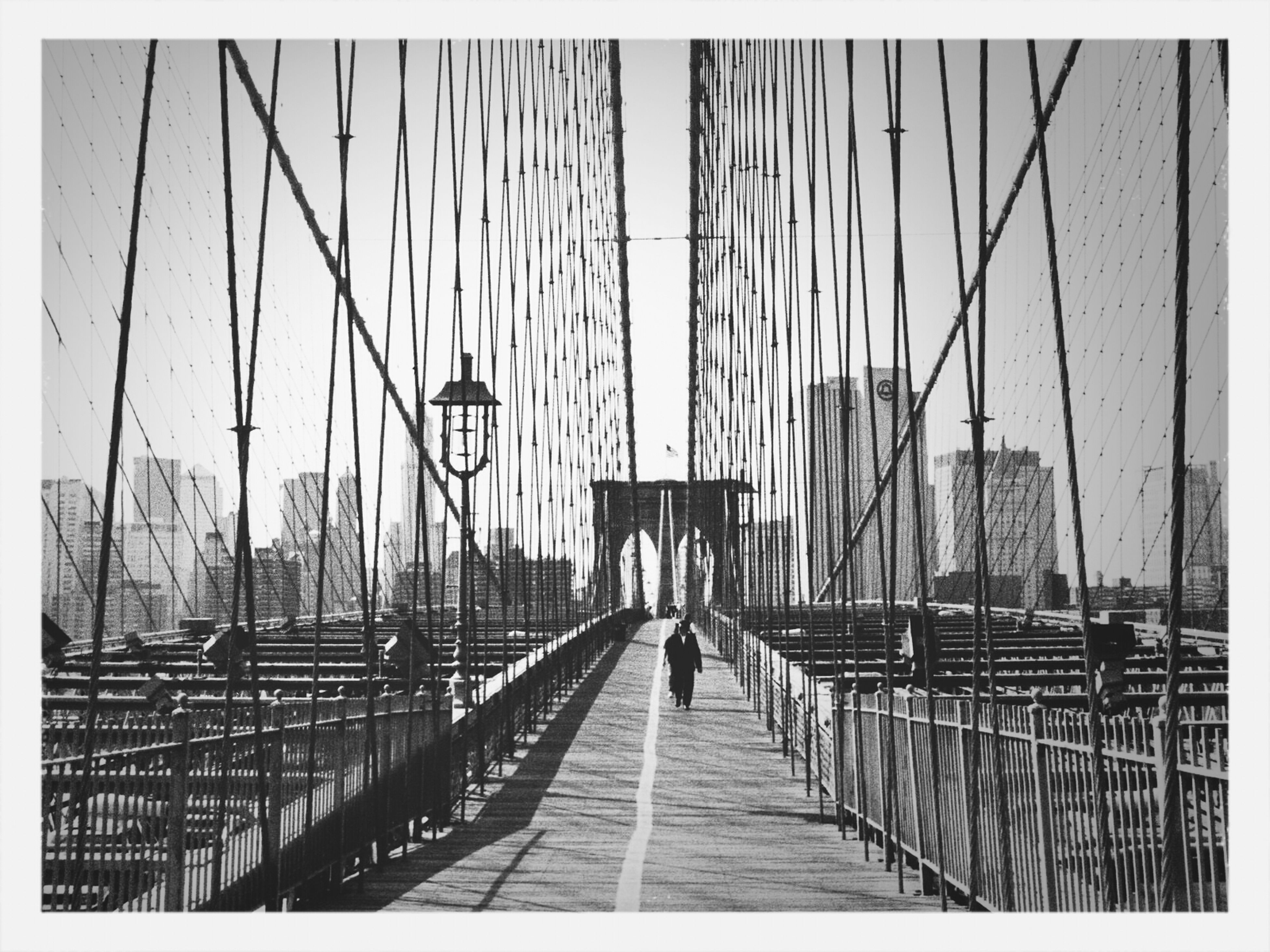 built structure, transfer print, walking, architecture, men, railing, lifestyles, the way forward, city, auto post production filter, transportation, person, leisure activity, day, city life, full length, building exterior, clear sky, bridge - man made structure
