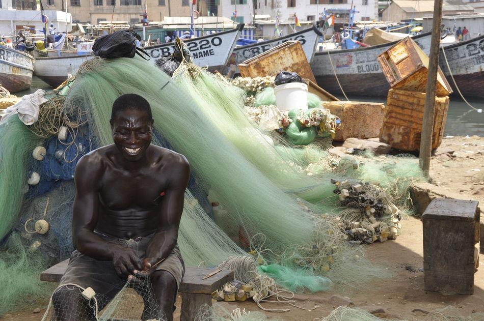 Fisherman repairing his nets Africa Boats Developing Country Fisherman Fishing Fishing Boat Fishing Net Fun Times Ghana Ghanaian Harbour In A Good Mood :)  Laughing Man Muscular Muscular Build Poor  Poverty Repairing Smiling Smiling Face To Repair WestAfrica Working