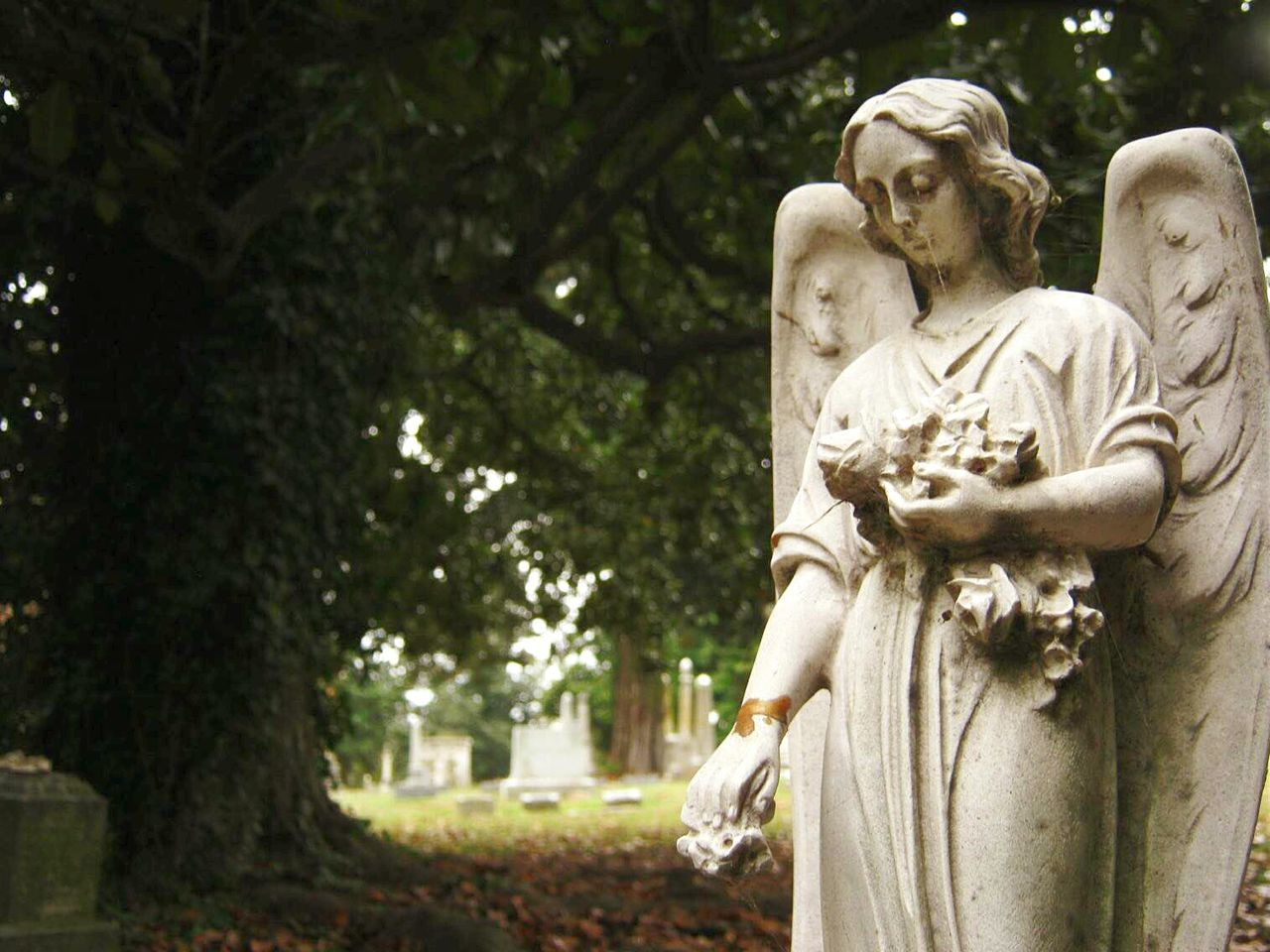 Low Angle View Of Statue In Cemetery