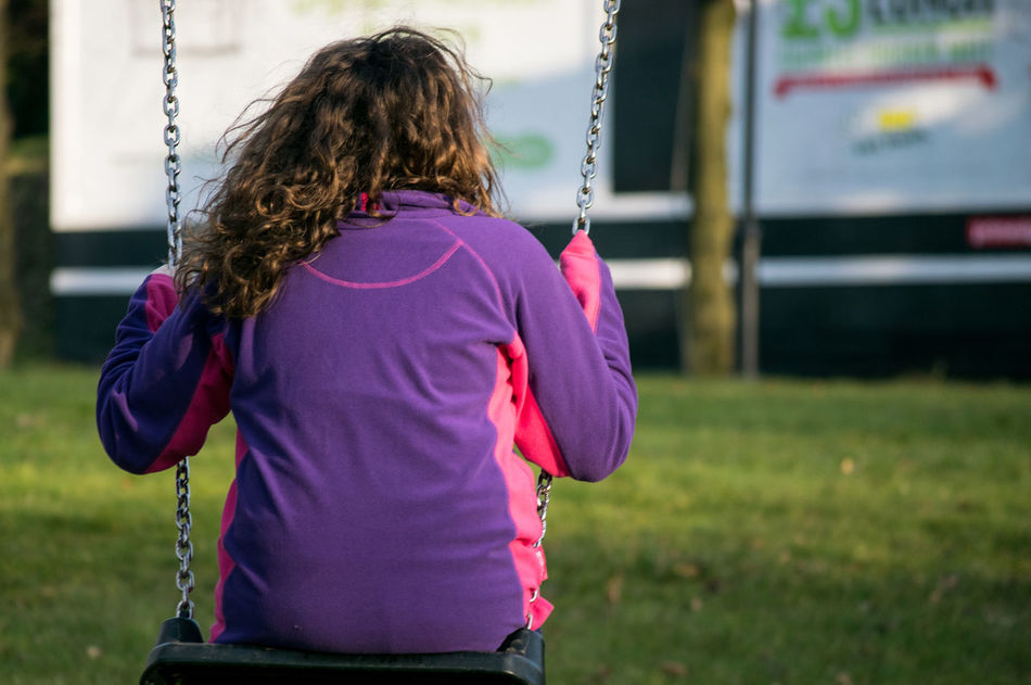 Girl Swing Outdoors Outside Human Hair From Behind Deprived Area Billboard Horizontal Colour Image Holding Human Hand Real People Child Sitting One Person One Child Day Chain Playground Park - Man Made Space Swingpark Jumper Swinging Childhood