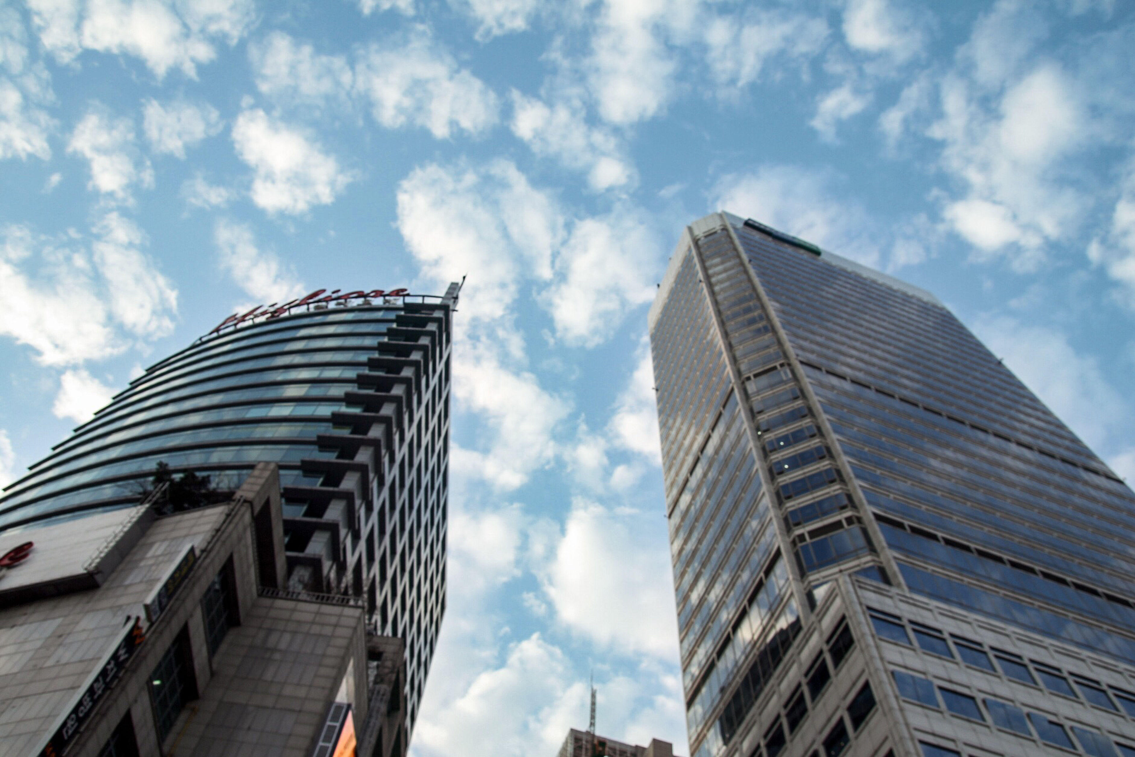architecture, building exterior, built structure, low angle view, skyscraper, modern, office building, city, tall - high, sky, tower, cloud - sky, glass - material, building, reflection, cloud, tall, day, cloudy, outdoors