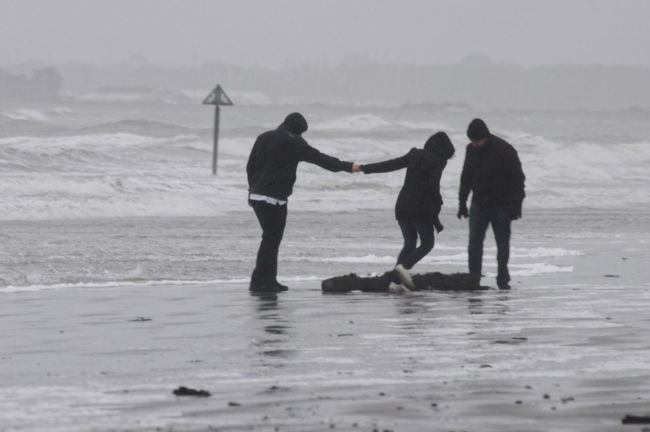 Three people playing on a beach in stormy winter weather. The waves have deposited some debris on the beach Beach Cold Debris Flotsam & Jetsam Grey Holding Hands Laughing Miserableweather People Playing Stormy Waves Winter