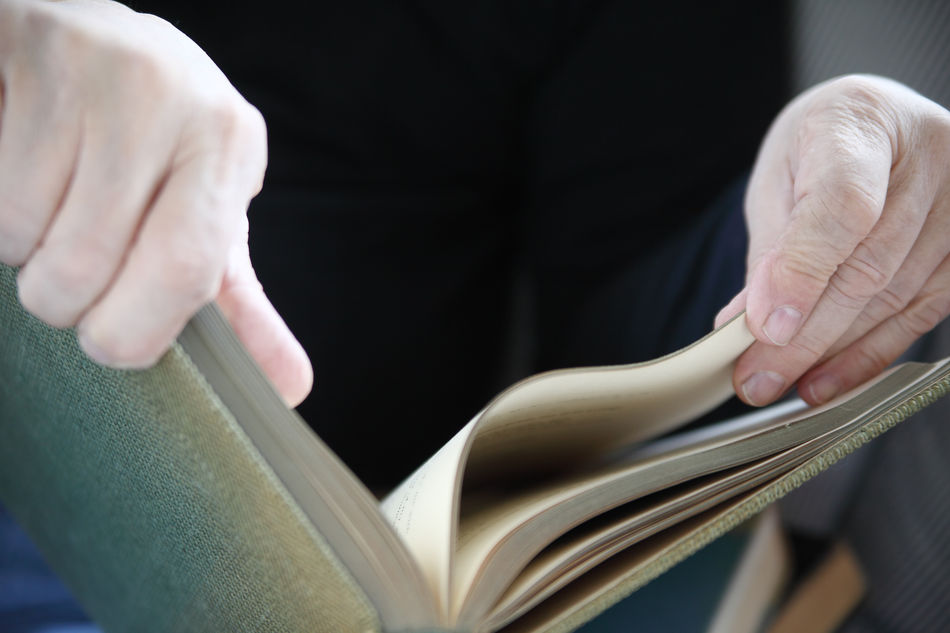 A man turns the pages of an old book. Book Close-up Fingers Hands Indoors  Information Knowledge Learning Literacy Literature Man Natural Light Pages Of A Book Paper Perusing Reading A Book Research Senior Sunny Text Space Turning Unrecognizable Person