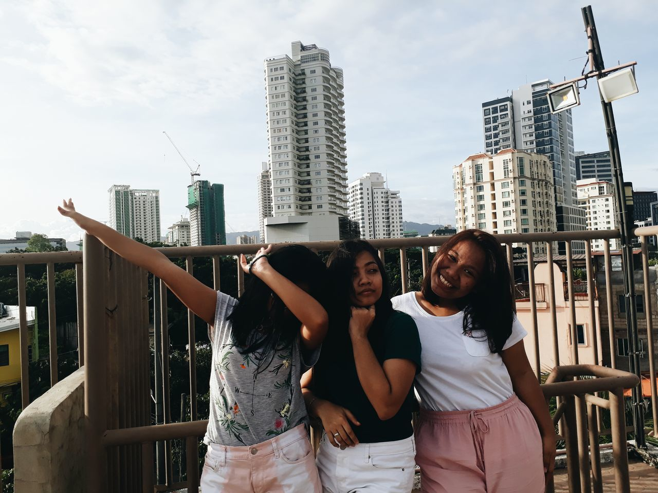 real people, building exterior, built structure, architecture, city, leisure activity, togetherness, two people, casual clothing, young women, front view, lifestyles, outdoors, skyscraper, standing, day, young adult, friendship, sky, bonding, smiling