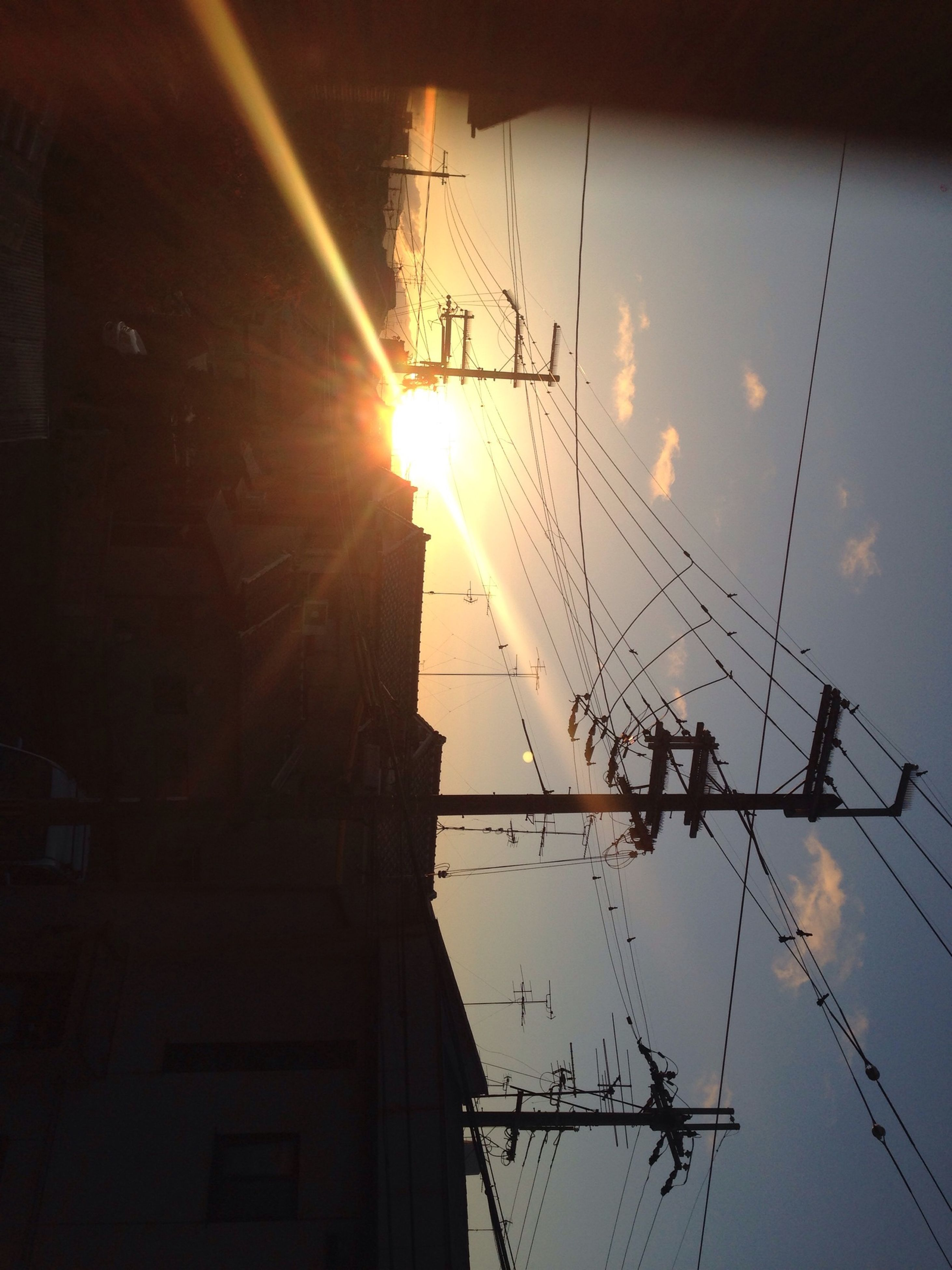 low angle view, electricity, power line, fuel and power generation, power supply, sun, silhouette, electricity pylon, technology, sky, cable, built structure, connection, sunset, sunlight, architecture, lighting equipment, sunbeam, outdoors, no people