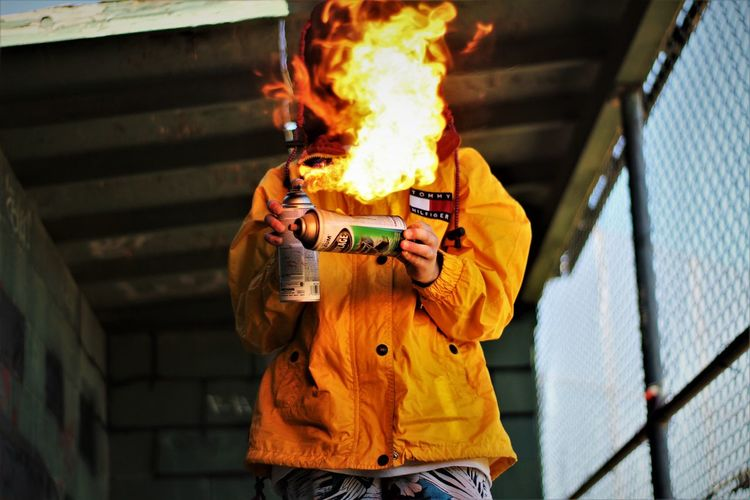 Burning Camera - Photographic Equipment Casual Clothing Flame Heat - Temperature Holding Lifestyles Men One Person Outdoors People Photographing Real People Young Adult
