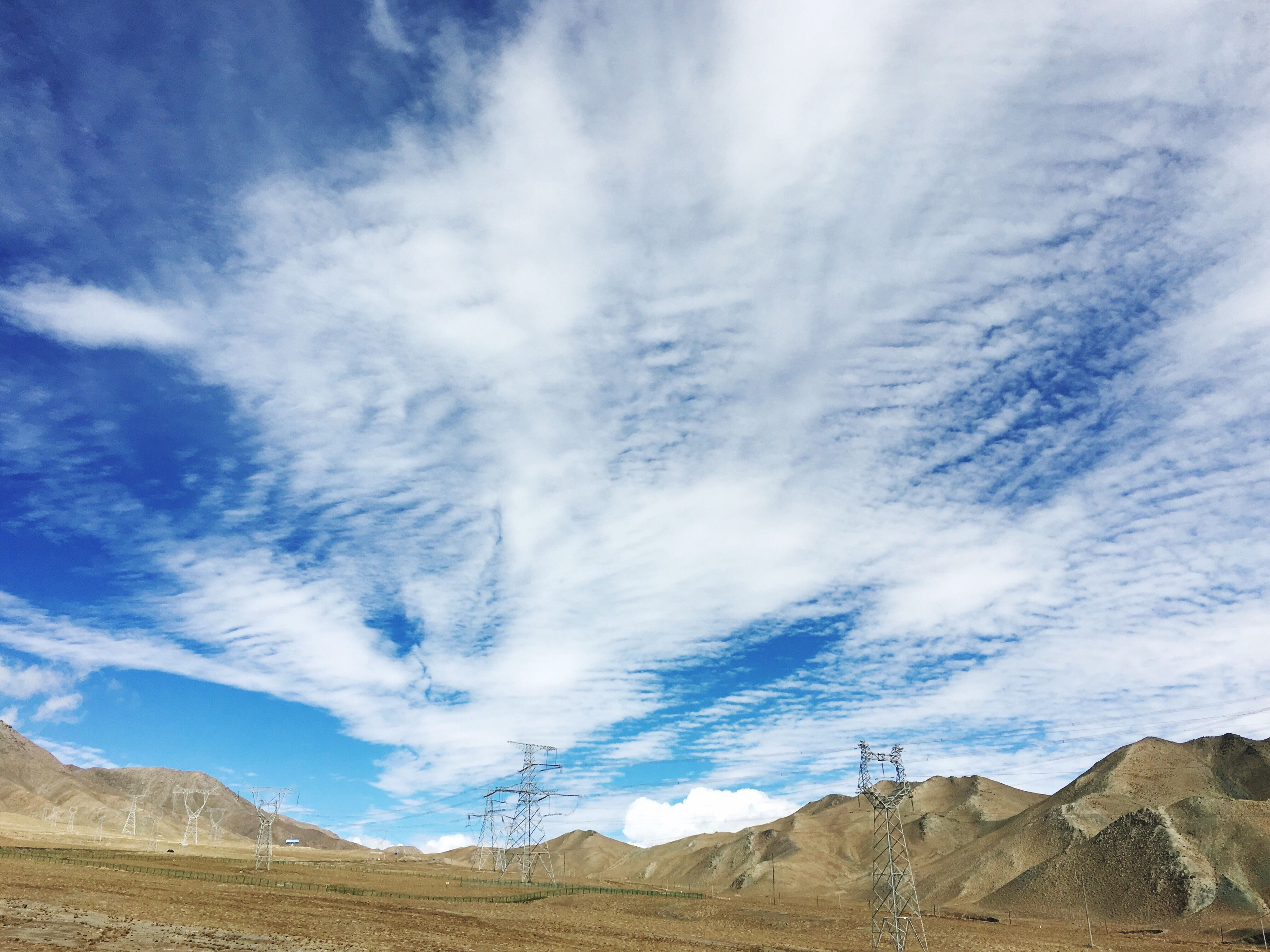 sky, low angle view, blue, mountain, scenics, day, beauty in nature, nature, outdoors, cloud - sky, cloud, tranquility, tranquil scene, mountain range, no people