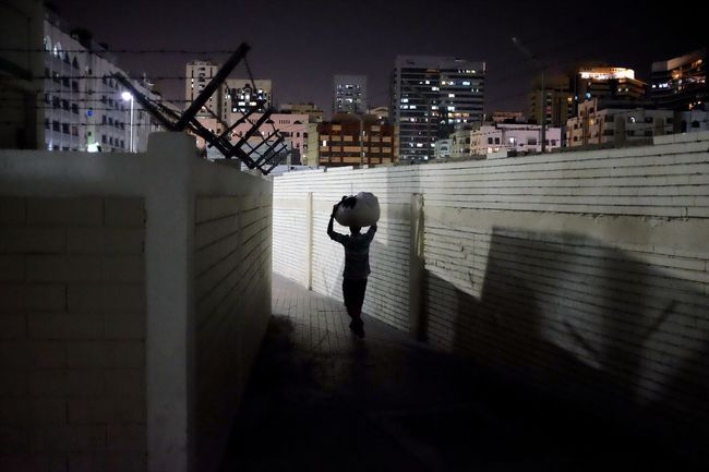 A man carries a parcel on his head while walking in the Madinat Zayed neighborhood of Abu Dhabi, UAE. Image © Brian Kerrigan 2016 Abu Dhabi After Dark Alley Architecture Built Structure Carrying City City Life Development Illuminated Night UAE Walking Around Walls