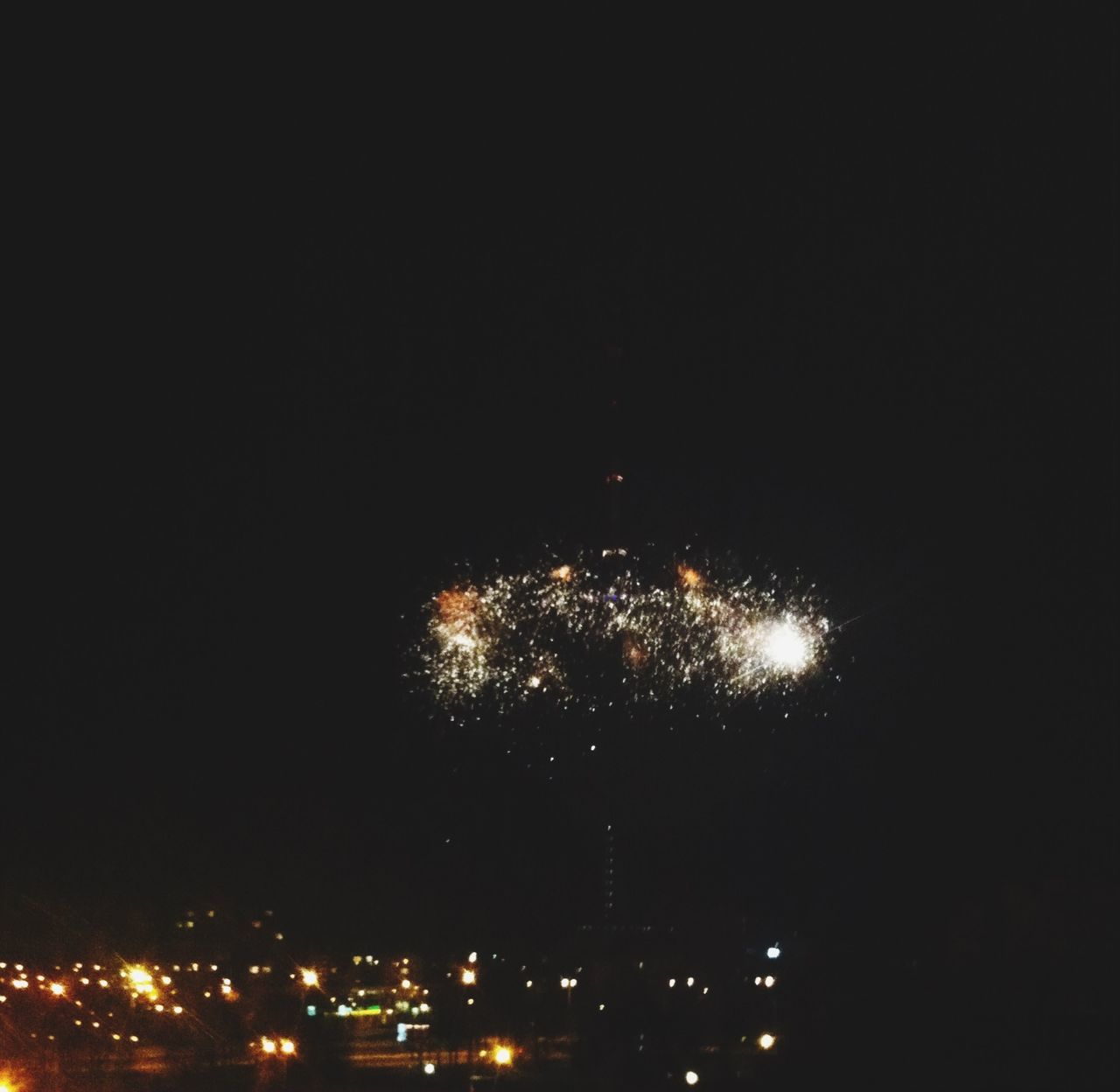 Defocused Image Of Firework Display Over City At Night