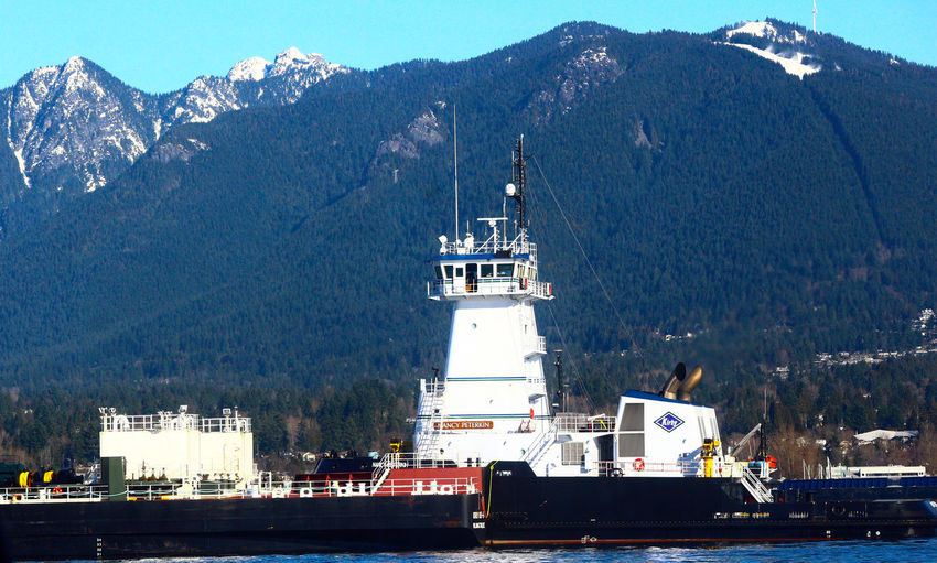 Cargo ship anchored in Burrard Inlet near North Vancouver B.C. North Vancouver Canada North Vancouver B.C. Lonsdale Quay Mountains Day Outdoors Architecture Mountain Building Exterior No People Tree Water Nature
