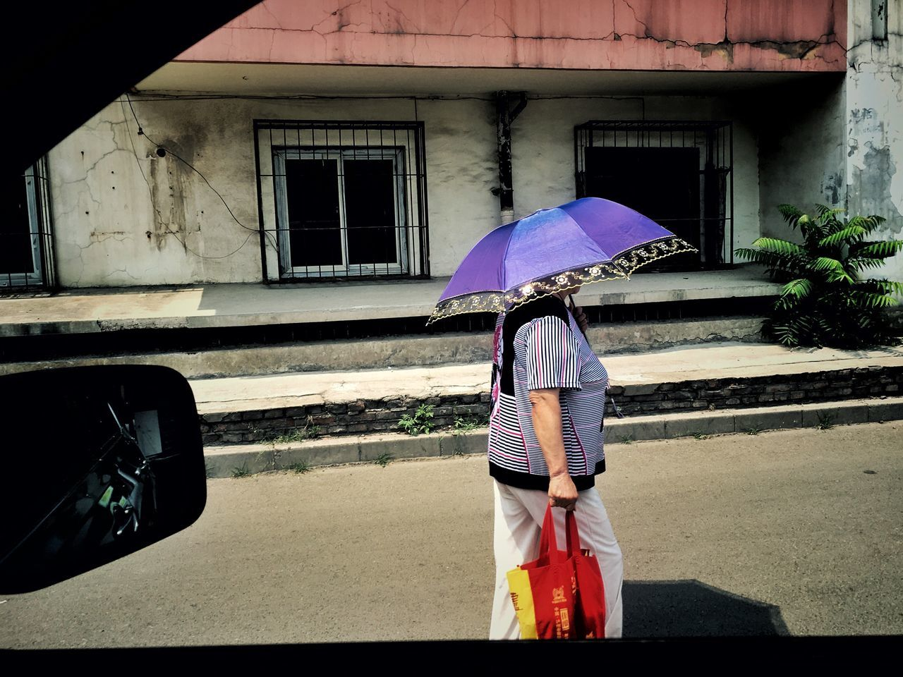 Side View Of Woman Holding Umbrella While Walking On Street Seen Through Car Window